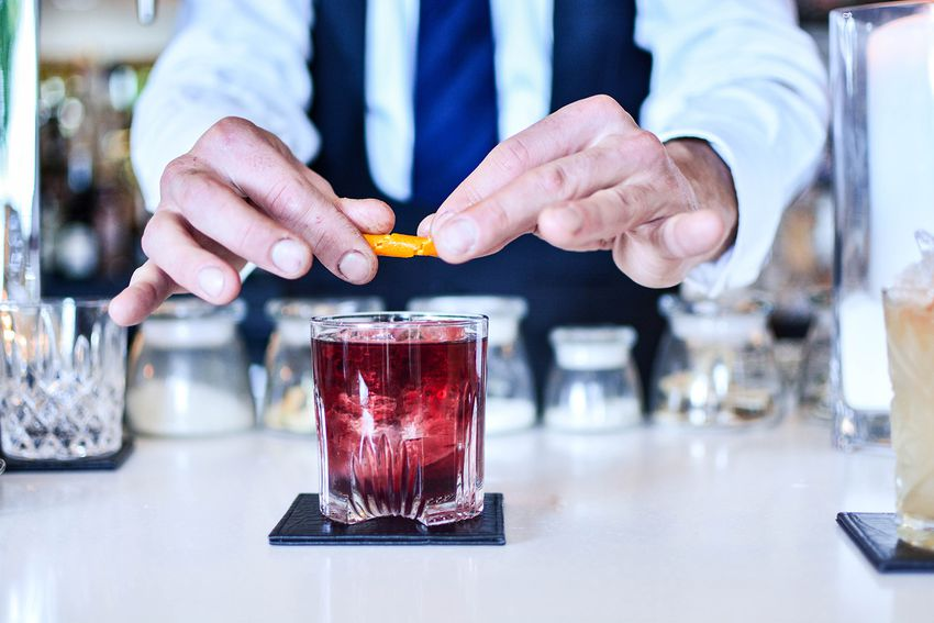 Midsection Of Bartender Preparing A Negroni At Restaurant