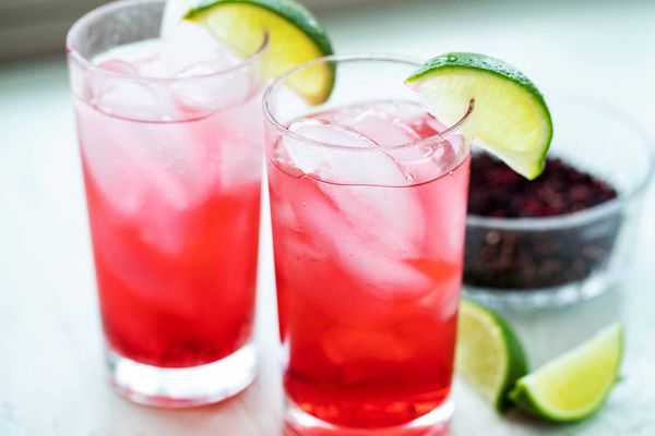 Horizontal view of two side by side tall glassed with hibiscus cocktails inside. Ice cubes are inside the glass and a lime wedge sits on the lip of each glass with additional lime wedges to the right of the glasses. Partial view of a bowl of dried hibiscus in the background to the right of the second glass.