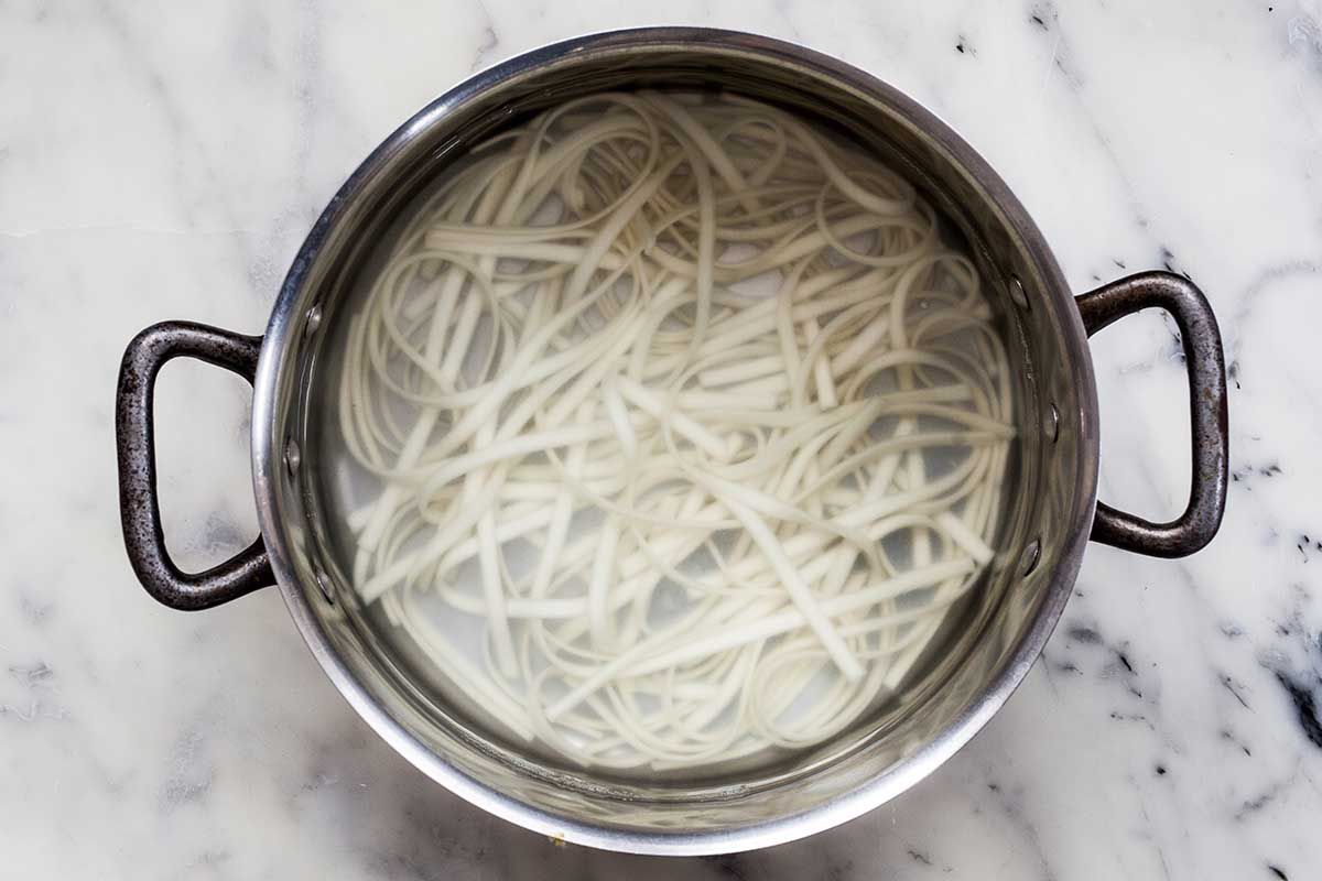 Udon noodles cooking in a silver soup pot.