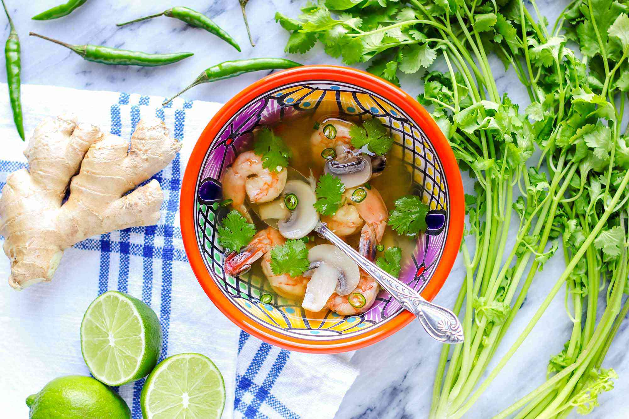 Thai soup with shrimp in a brightly patterned bowl with a silver spoon inside. Sliced limes, ginger, peppers and cilantro stems suround the bowl of light broth, shrimp, mushrooms and cilantro. The bowl is on a marble counter with a blue striped linen to the left of the bowl.