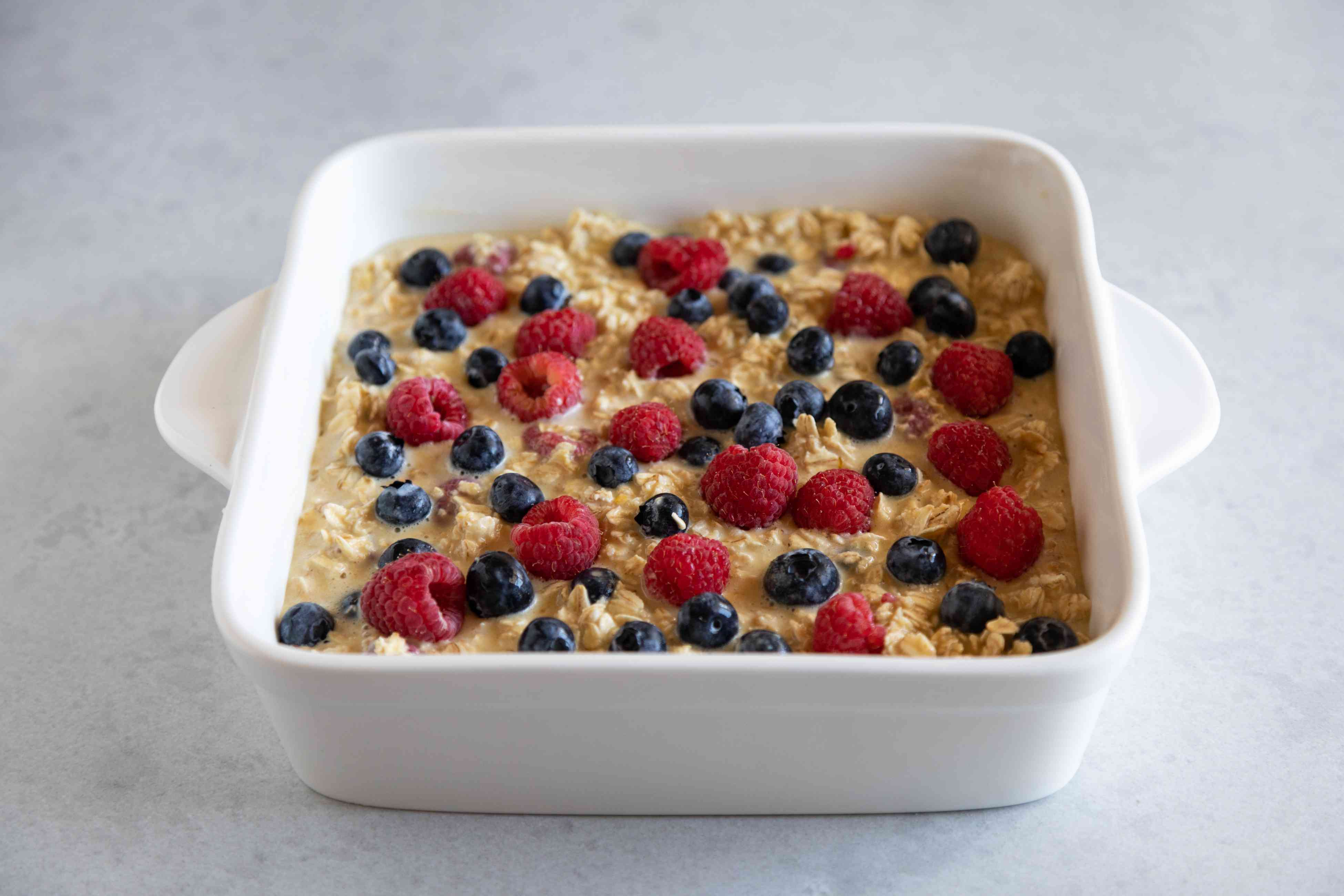 Mixed Berry Baked Oatmeal in a ceramic baking dish and ready to be baked.