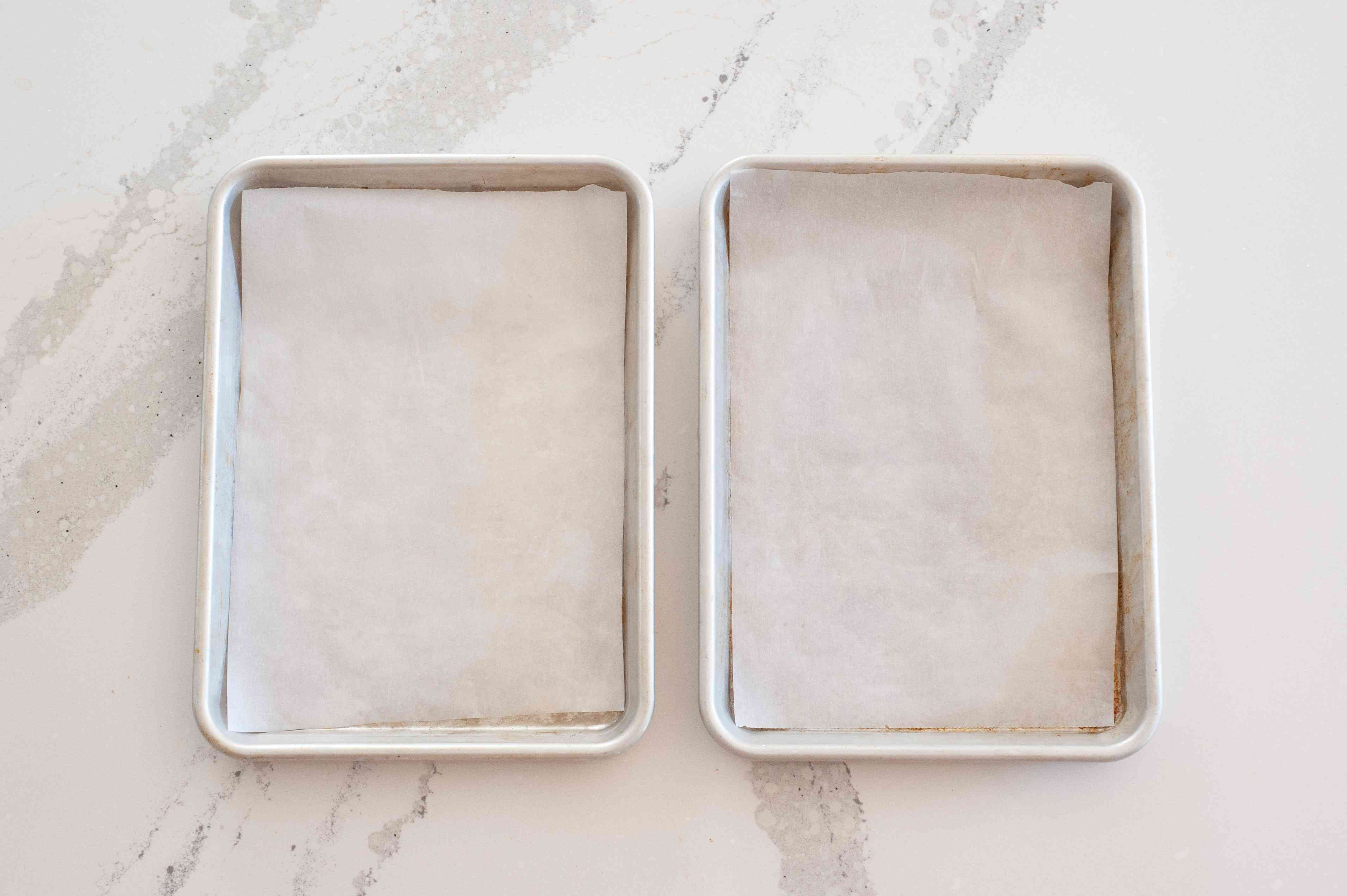 Overhead view of two parchment lined baking sheets.