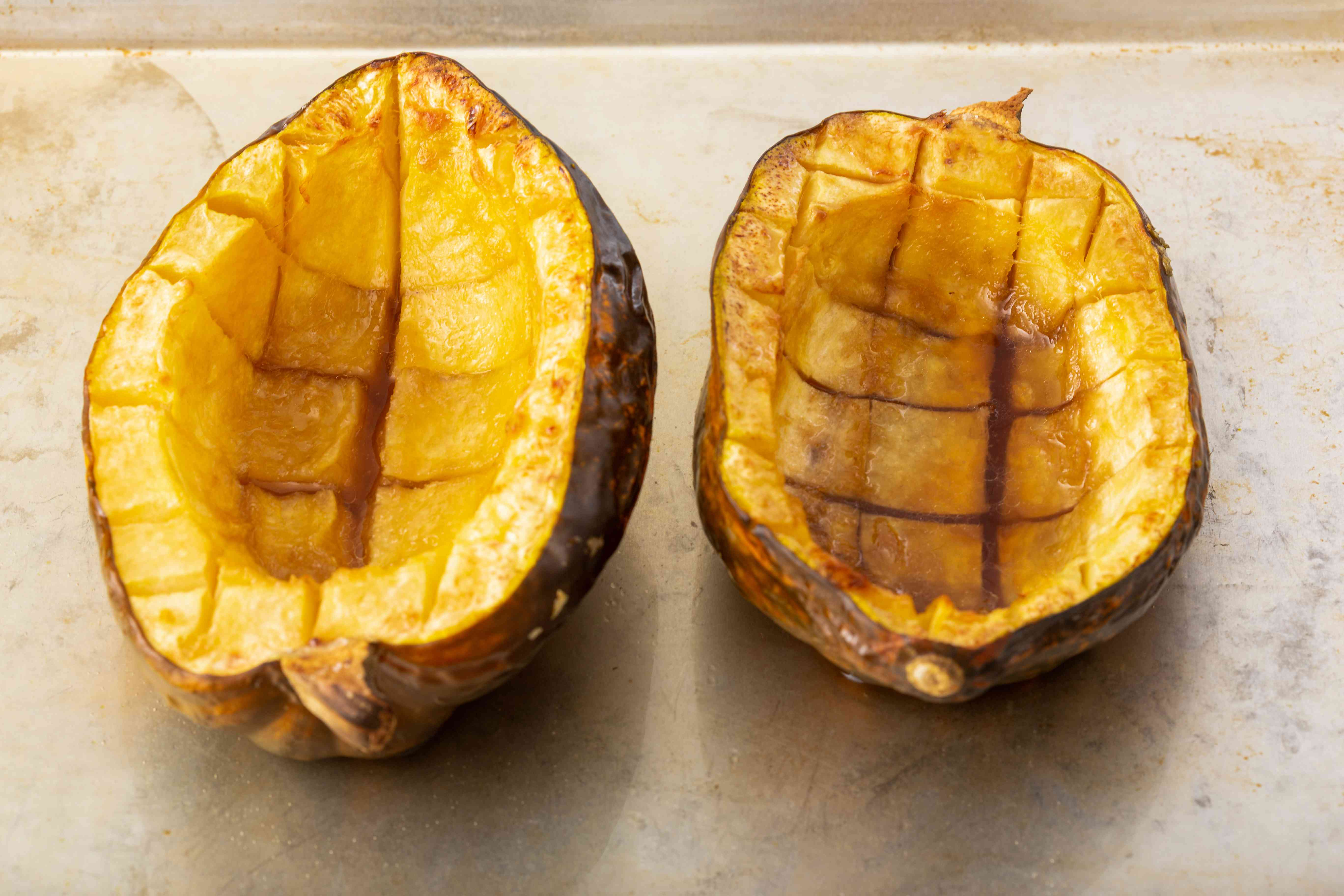 Two halves of roasted acorn squash on a counter.