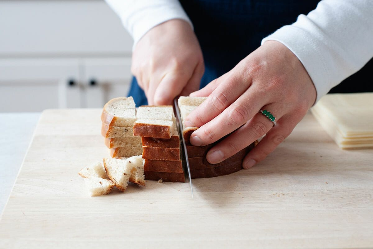 A person with a blue apron and long sleeved white shirt is holding a chef's knife and cubing rye bread on a wooden cutting board.