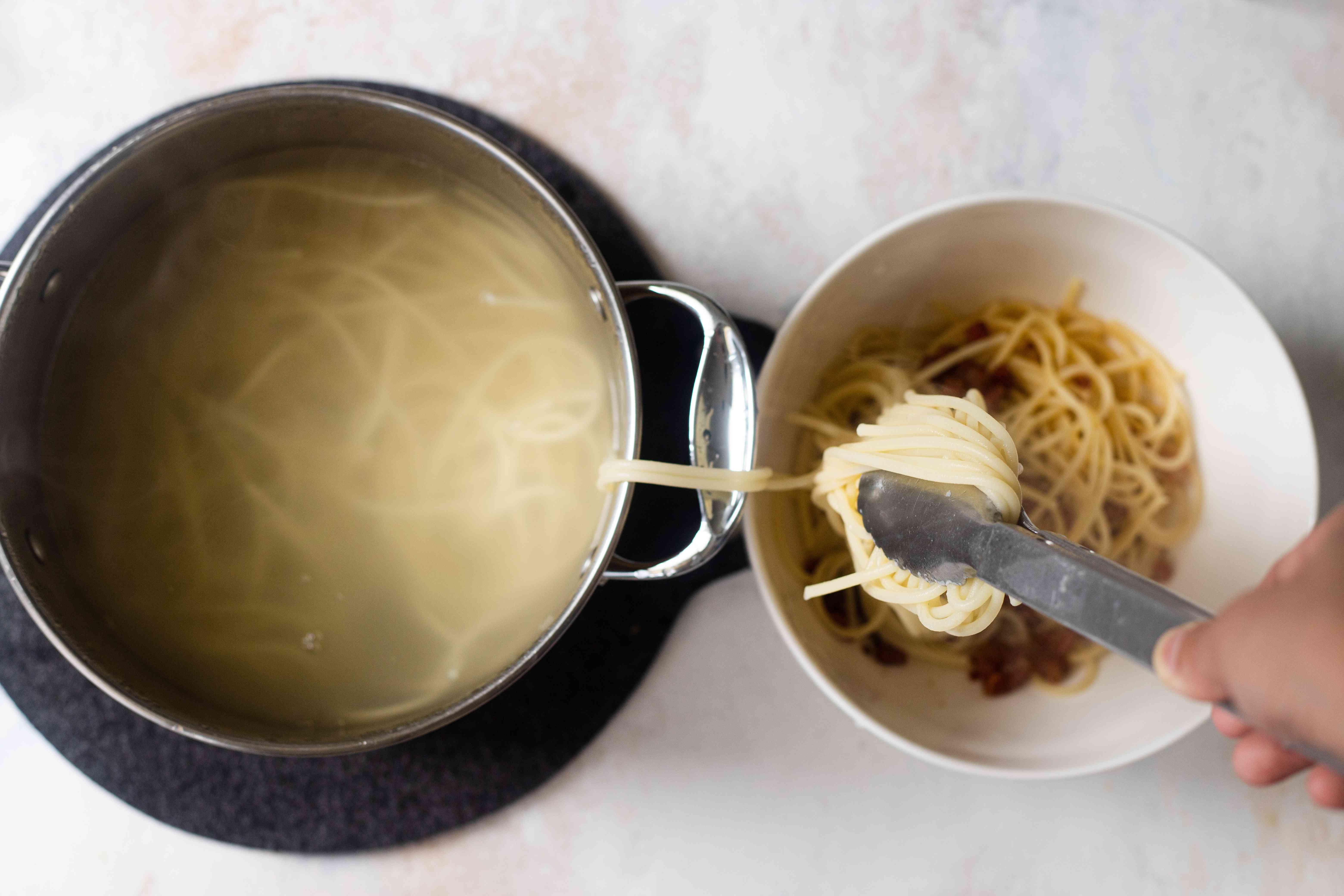 A pot of pasta with tongs moving the pasta to a bowl.