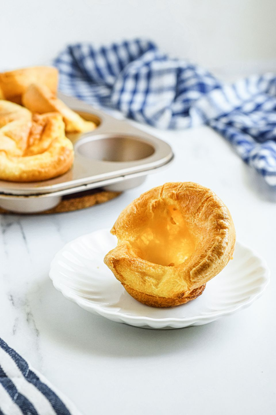 A plate with a yorkshire pudding on it and more in the background along with a striped linen.