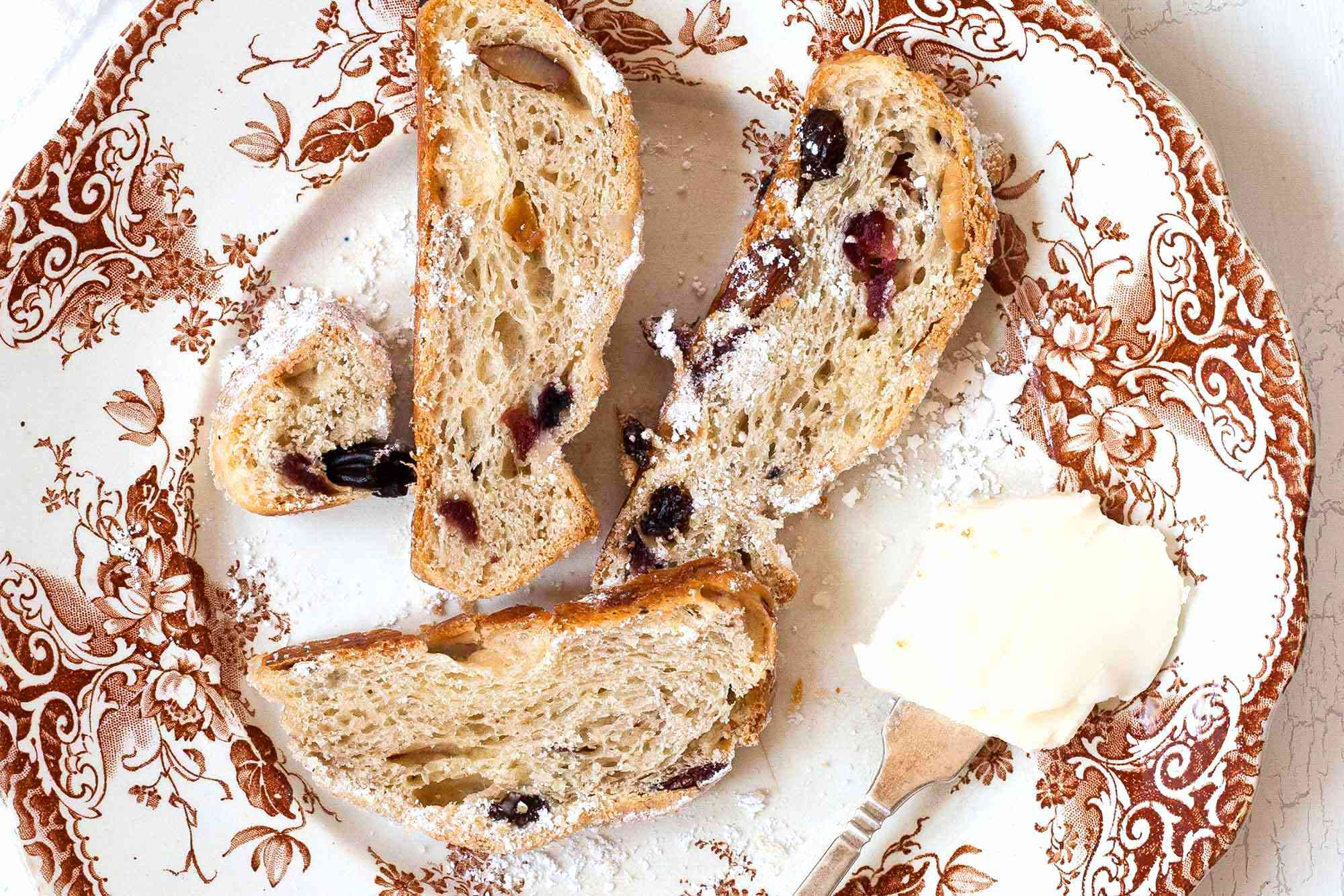 Stollen Christmas Bread filled with rum-soaked dried fruit coated with powdered sugar and sliced on a platter with a fine mesh sieve with powdered sugar in it nearby.