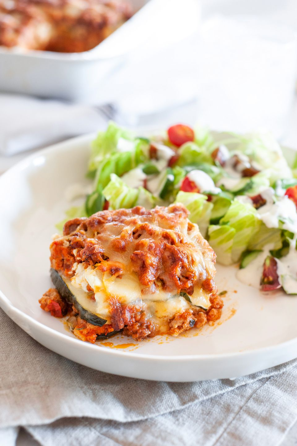 No noodle zucchini lasagna on a plate with a salad.