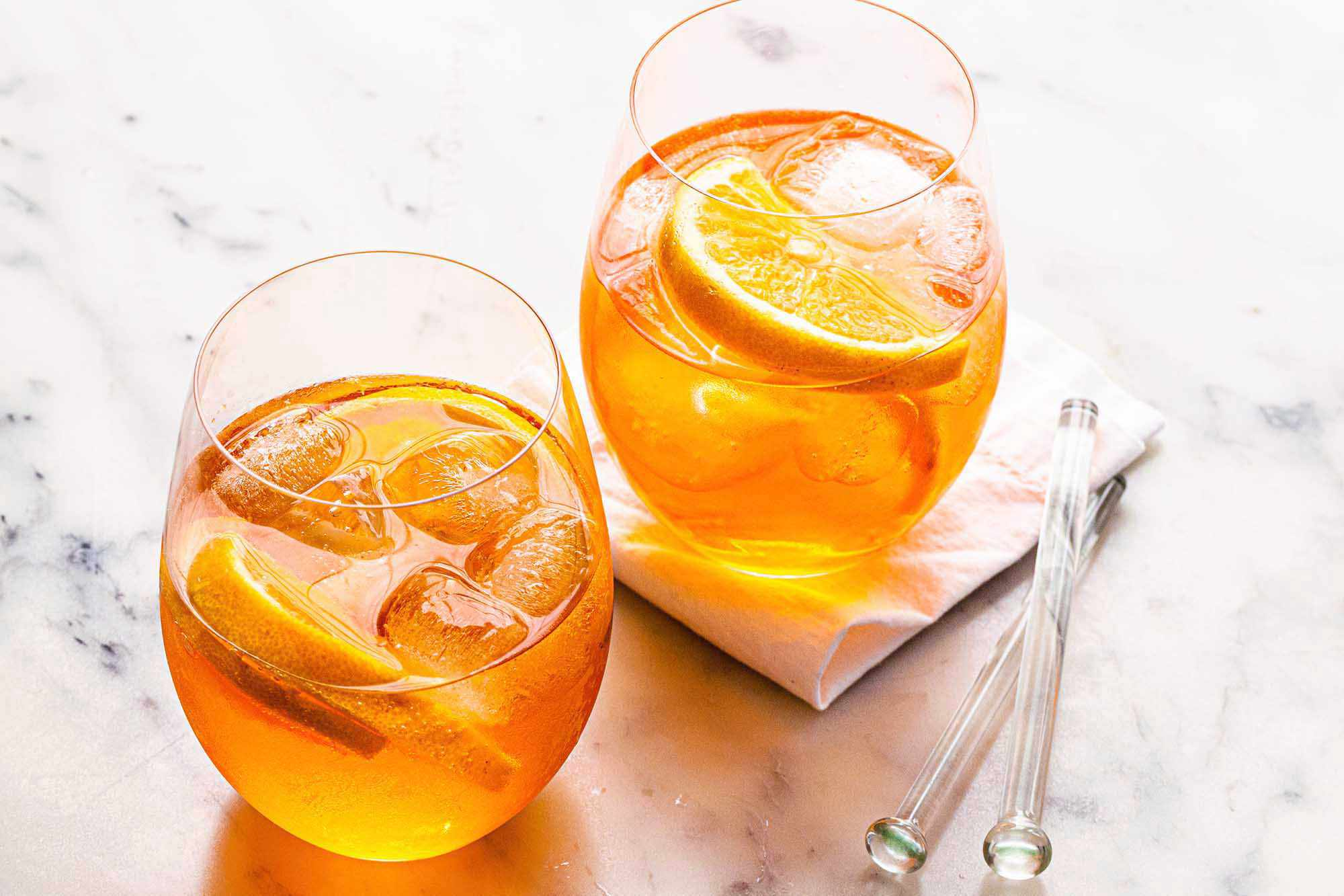 Two Aperol spritz cocktails on a table with ice and orange slices, a napkin and two stir sticks to the right.