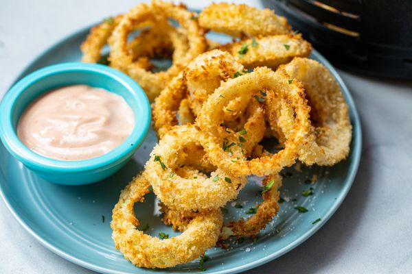 Crispy Air Fryer Onion Rings stacked on a plate with a dipping sauce.