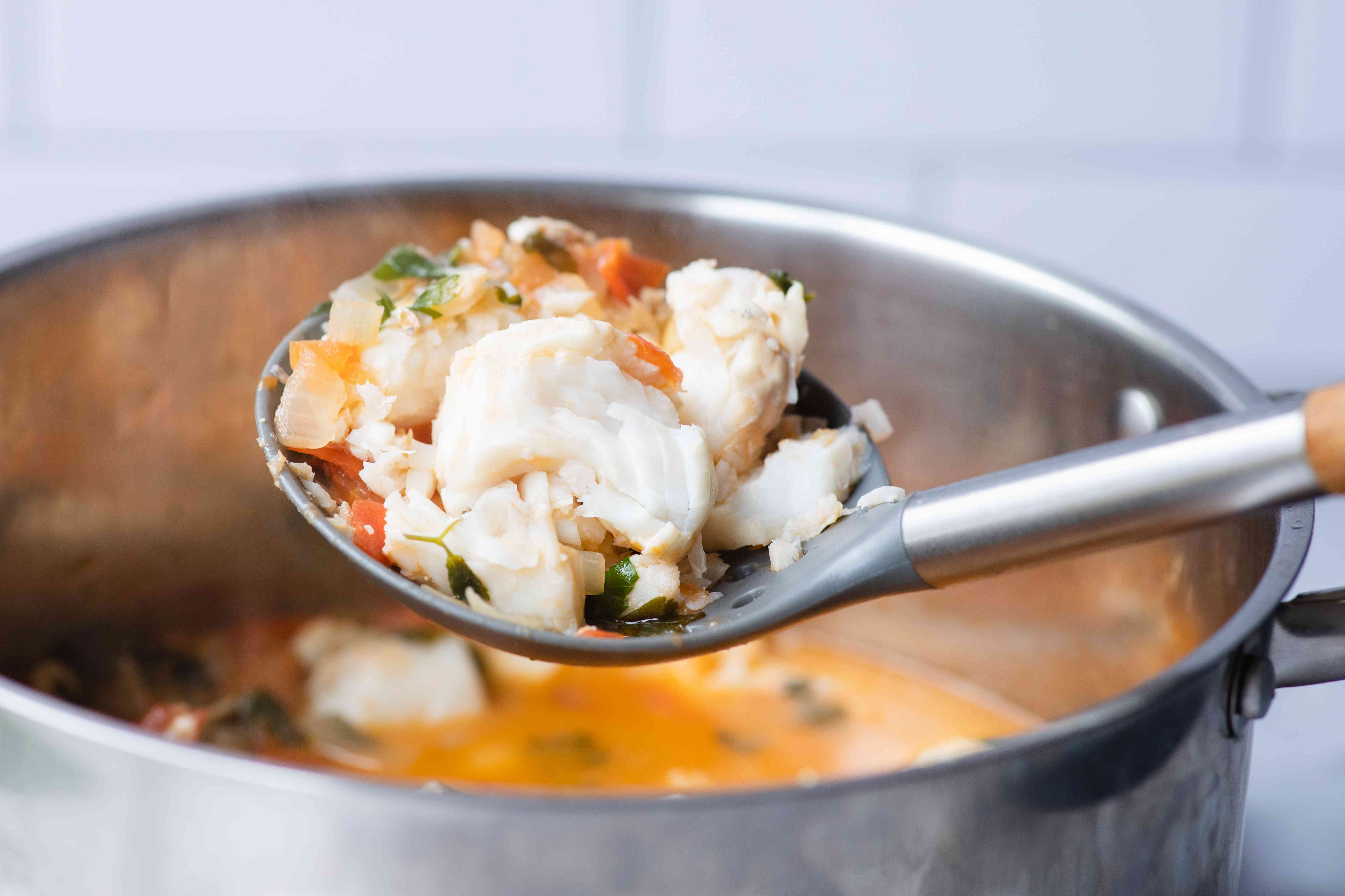 Ladling fish soup out of a pot.