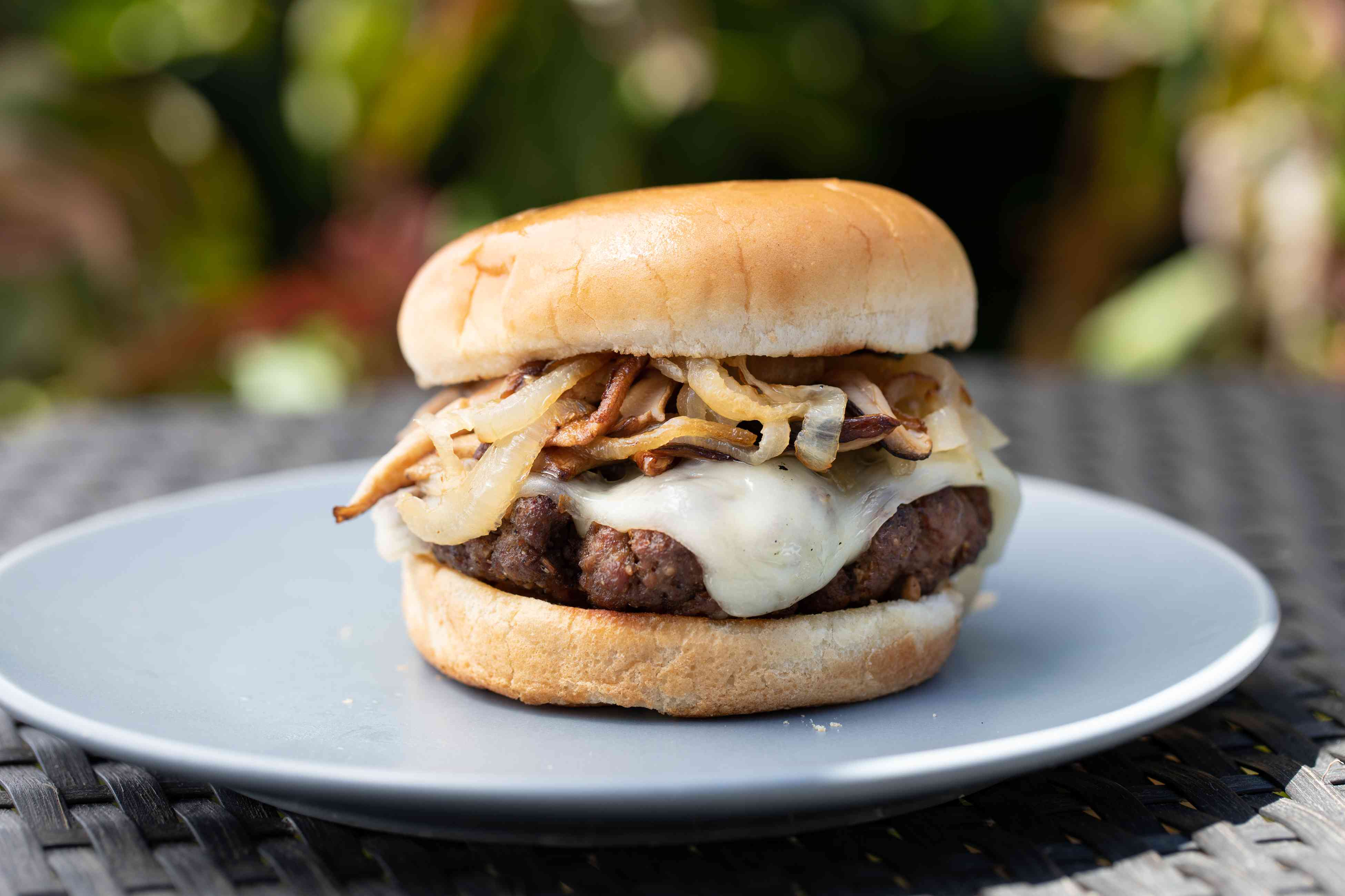 Side view of a mushroom swiss burger on a plate outside.