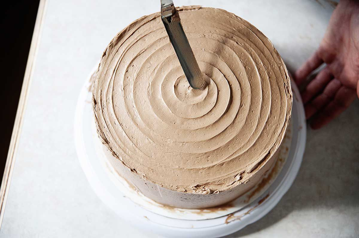 Woman using an offset spatulat to make a swirl in the chocolate swiss meringue buttercream frosting on top of a chocolate layer cake