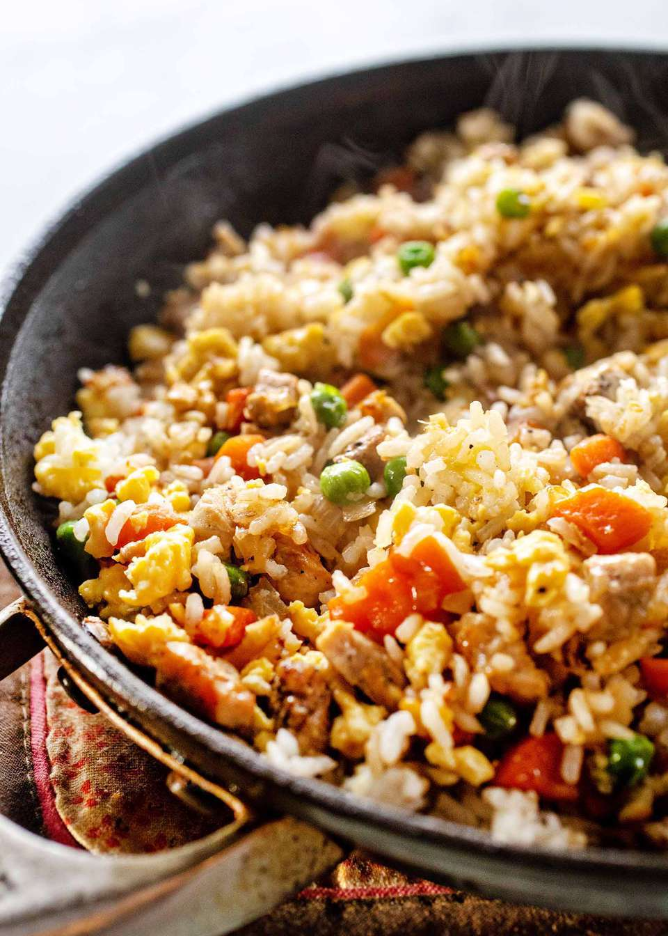 Black skillet with pork fried rice recipe cooking inside. Carrots and peas are mixed in the rice.