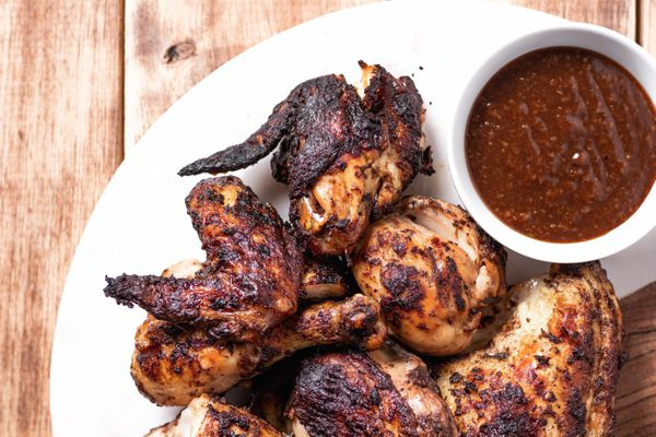 Overhead view of jerk chicken on a platter with dipping sauce.