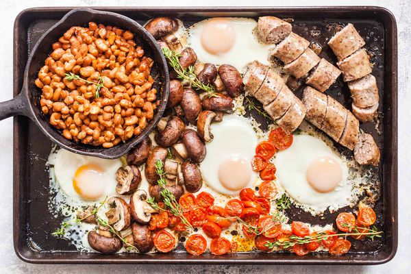 Full English Breakfast on a Sheet Pan -- a pot of beans, cracked eggs, sausages, potatoes, and tomatoes