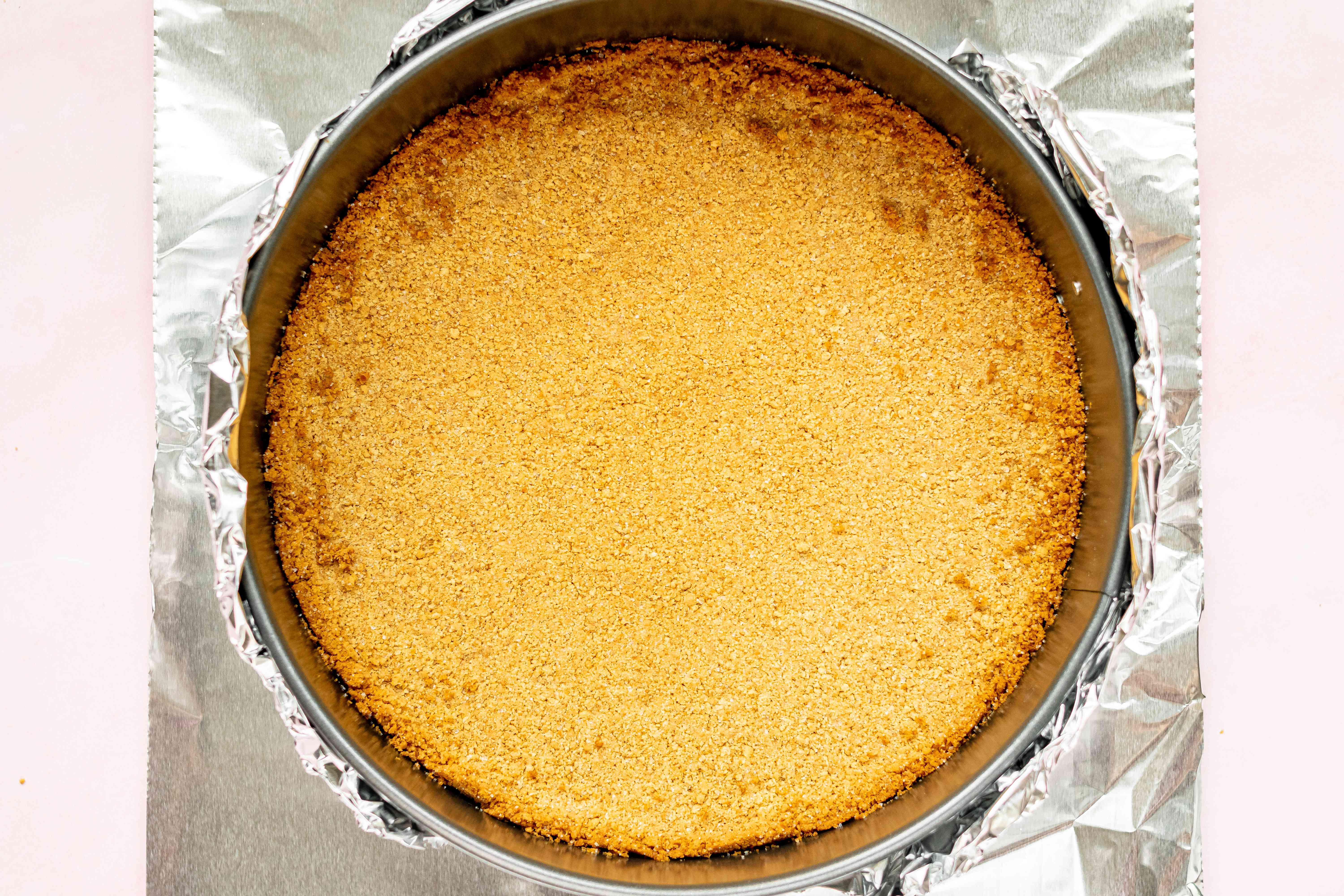Wrapping the springform pan in foil to make an easy cheesecake recipe.