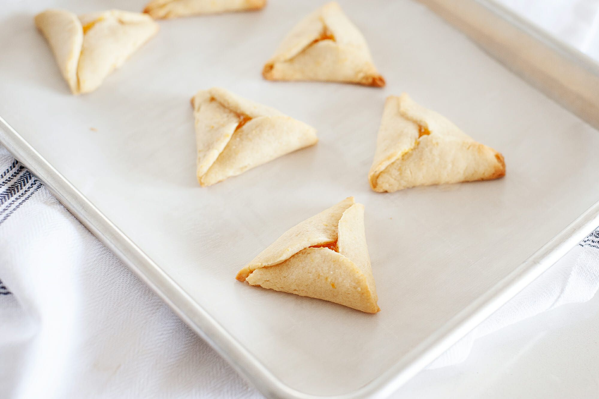 Apricot Hamantaschen set on a diagonal baking sheet with a white linen underneath.