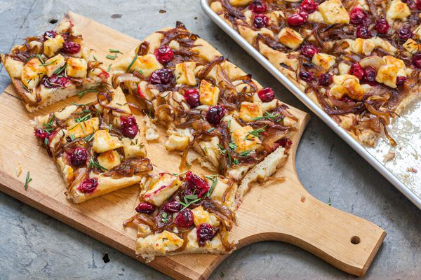 A cutting board with slices of focaccia topped with caramelized onions, cranberries, and brie.