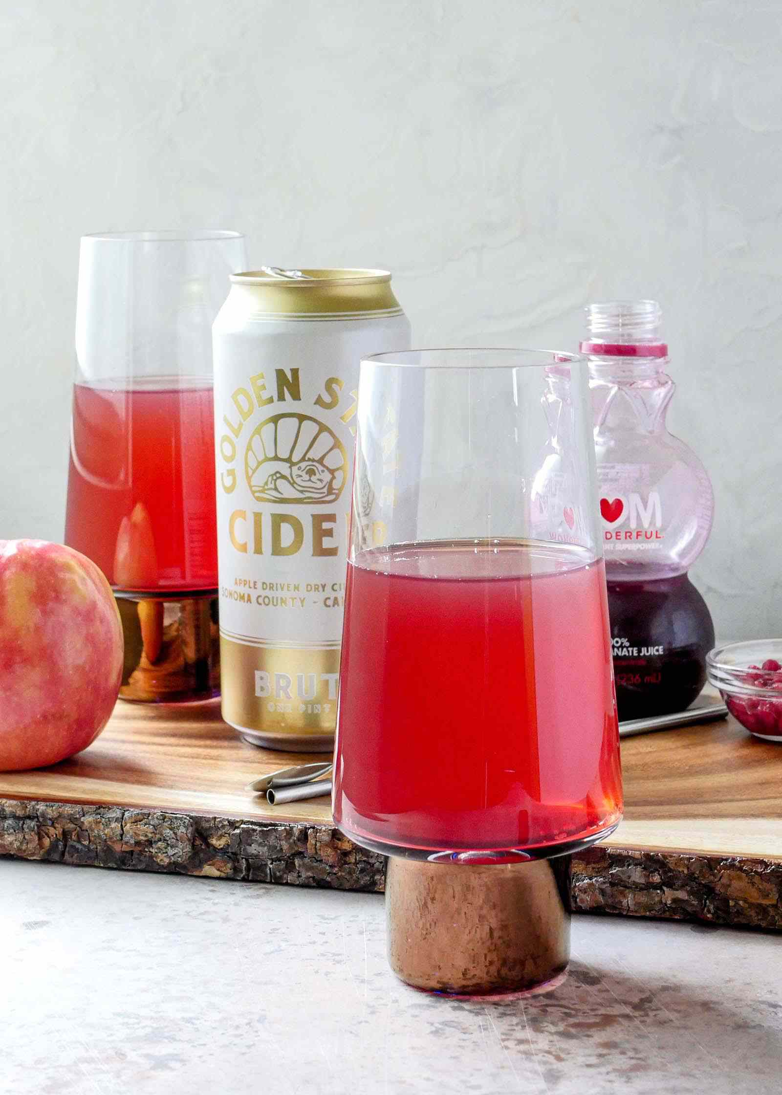 Ingredients for Pomegranate Mimosa with Hard Cider on a wooden board with an apple and a second mimosa interspersed.