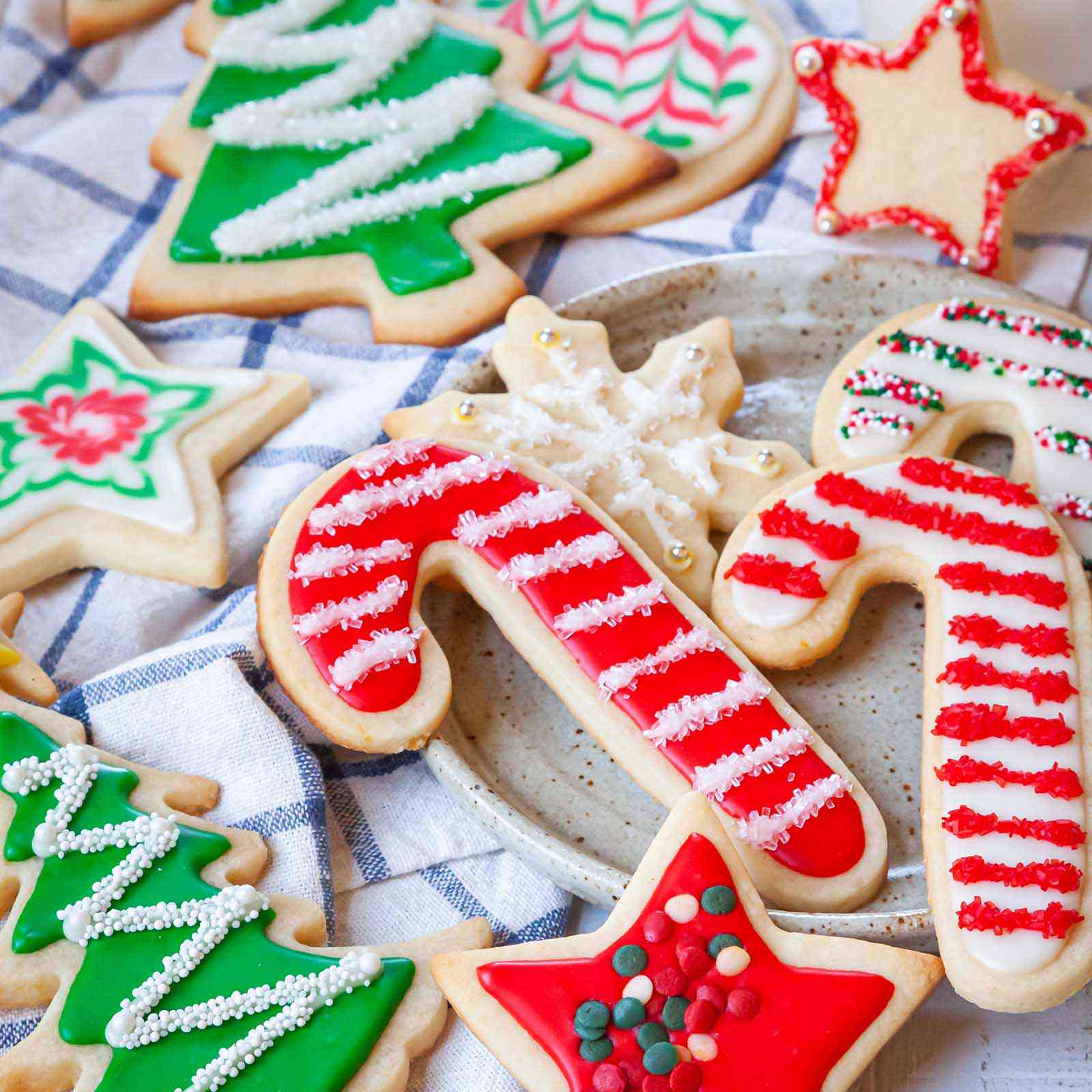 A variety of holiday cookies decorated with sprinkles and Easy Royal Icing recipe.