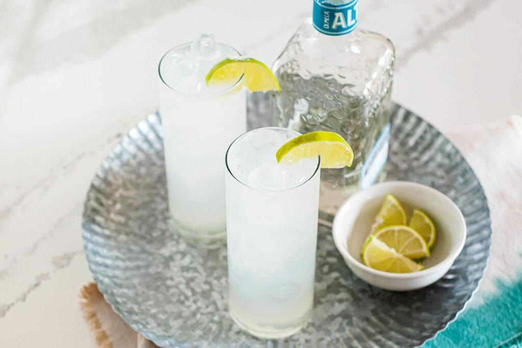 Paloma Cocktail Recipe - two tall glasses on silver tray with bottle and limes