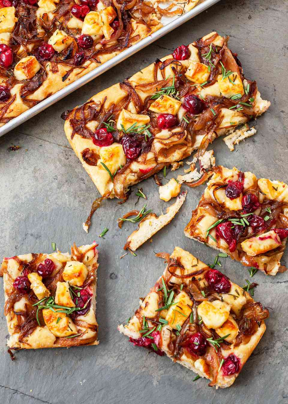 Slices of focaccia topped with caramelized onion, cranberry, and brie.