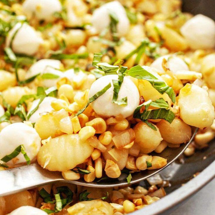 Sweet Corn Gnocchi Skillet Recipe - mozzarella gnocchi and corn on spoon with garnish