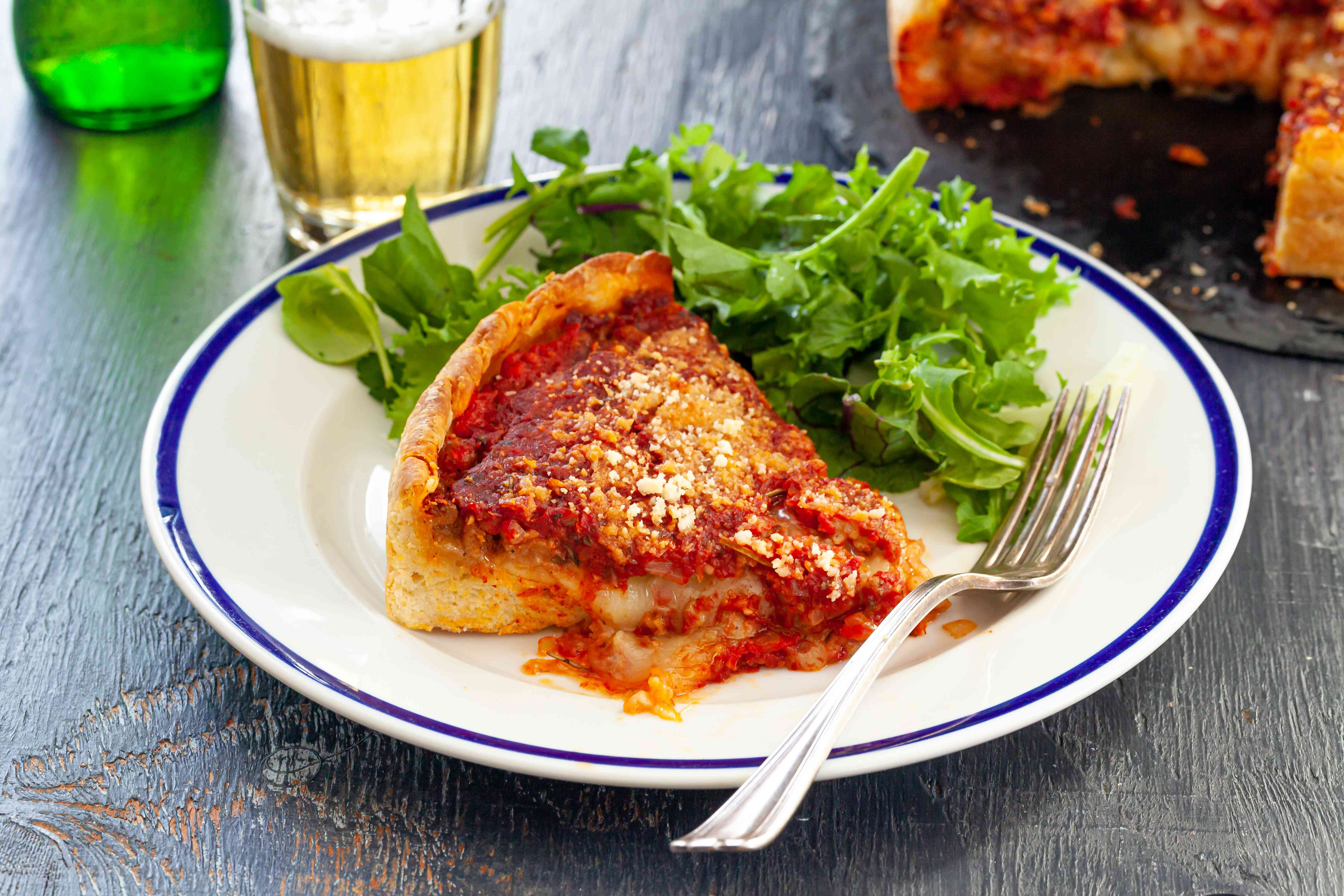 A slice of Italian Sausage Deep Dish Pizza on a plate with a salad.