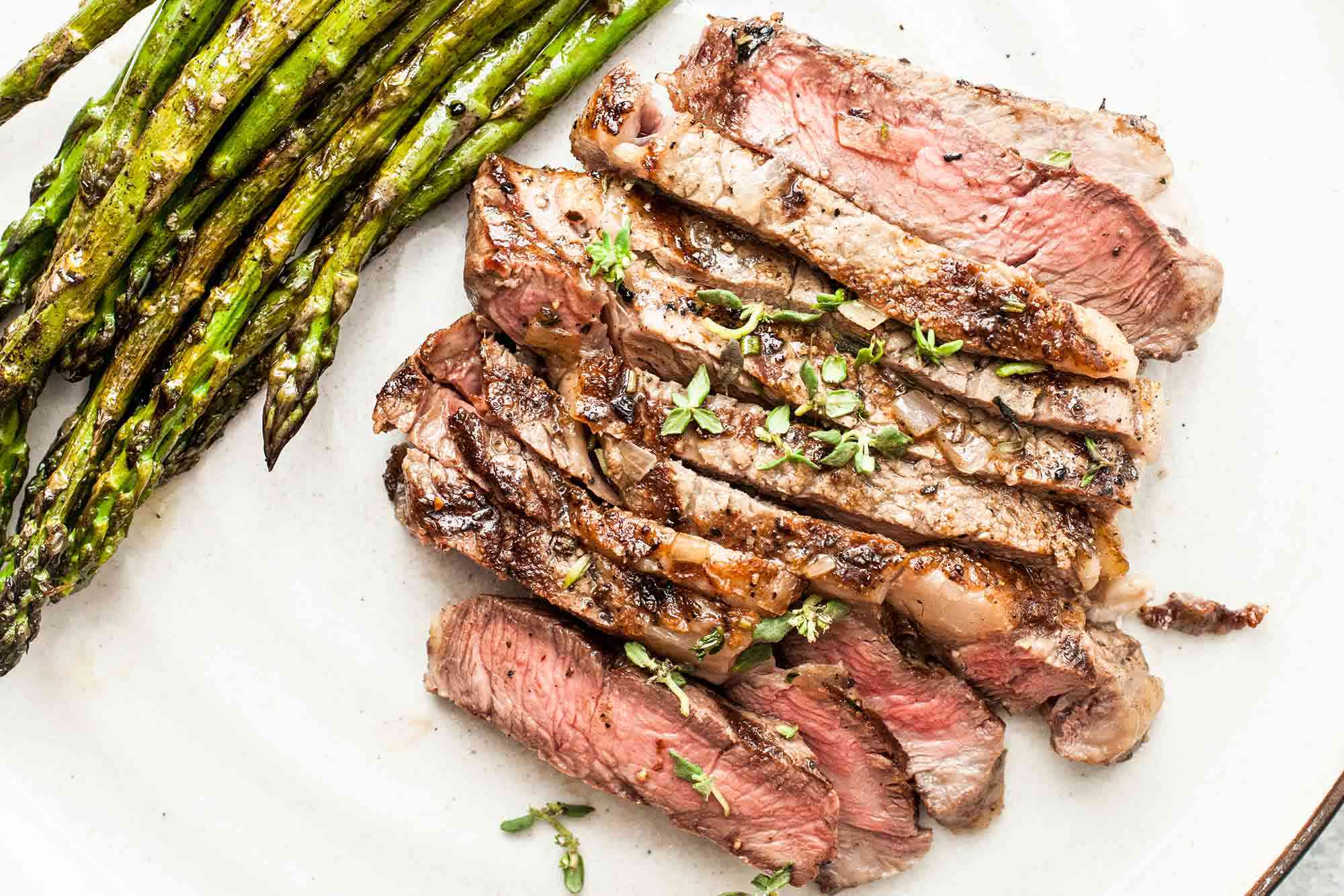 Grilled Ribeye Steak on a platter with asparagus