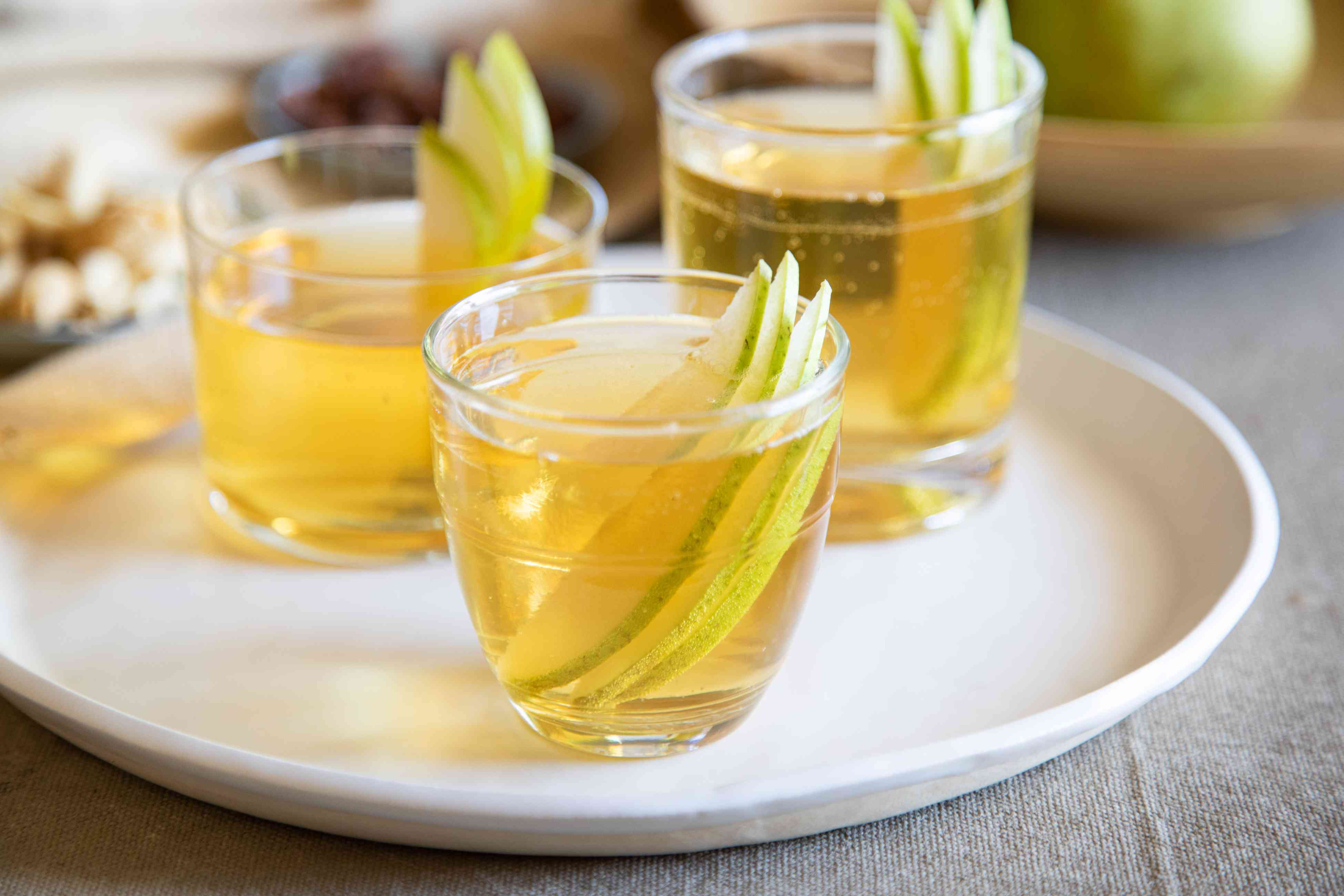 Three glasses of spiced pear bourbon punch on a tray.