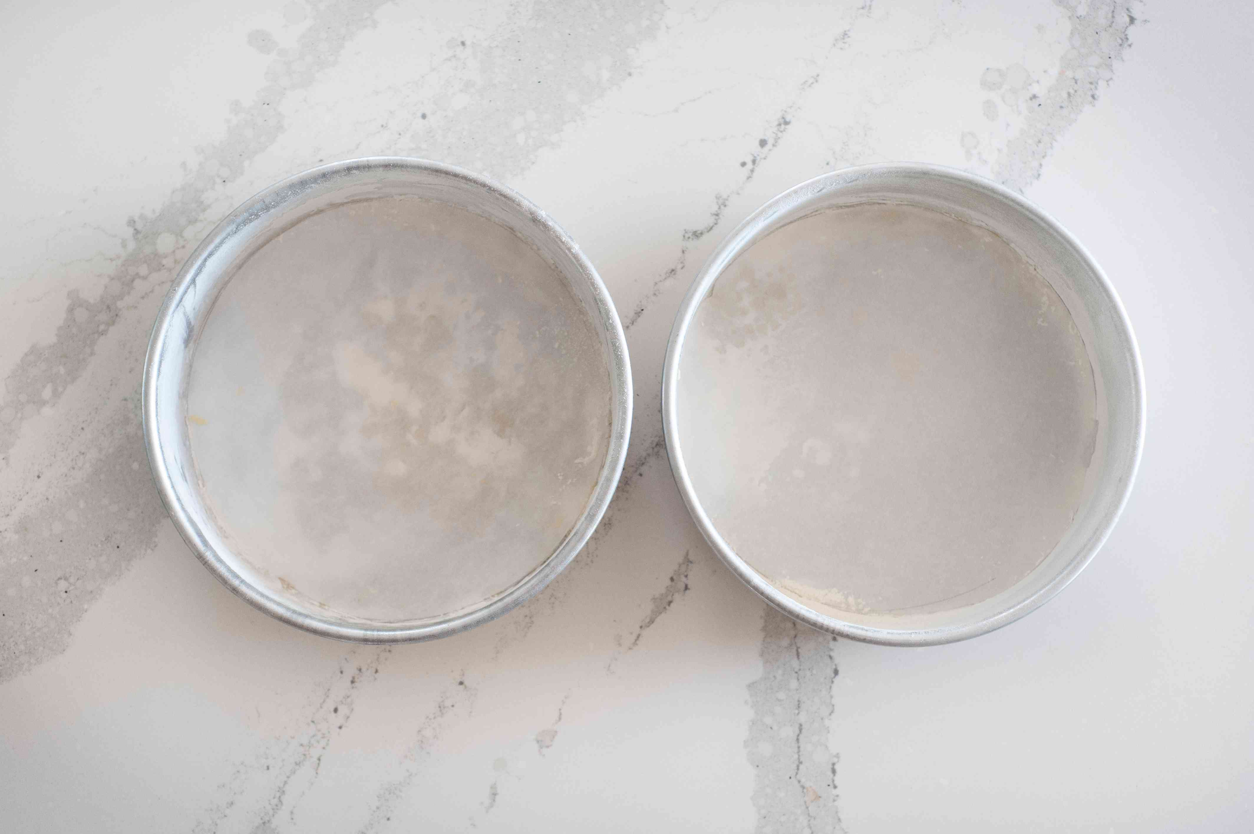 Two cake pans lined with parchment to make Fresh Strawberry Layer Cake with Seven-Minute Icing.