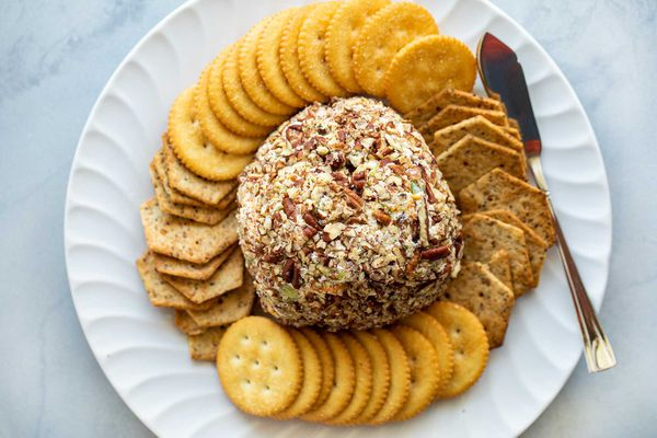 The best cheese ball is in the center of a platter and surrounded by crackers.