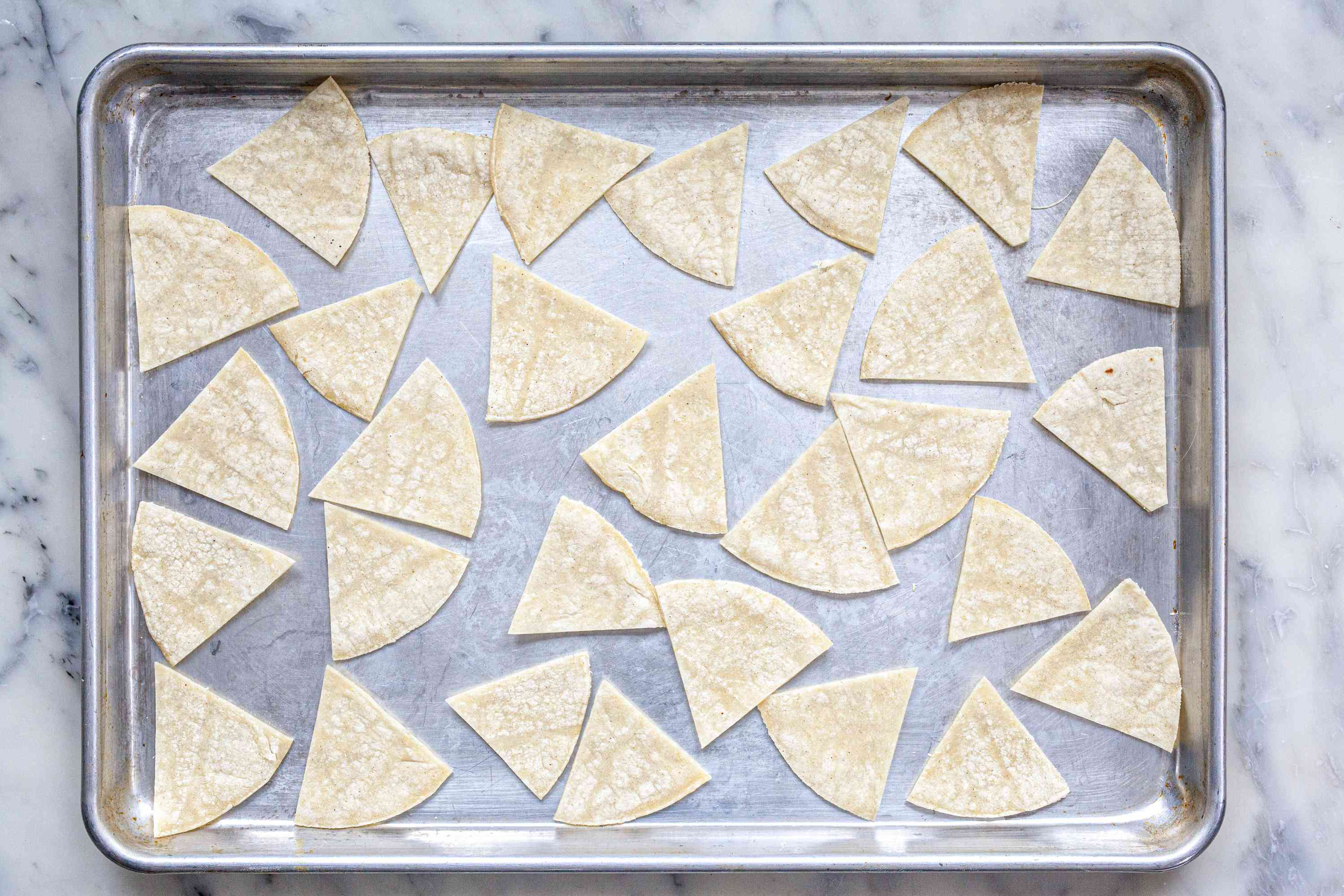 Tortilla wedges on a sheet pan to show how to make tortilla chips.