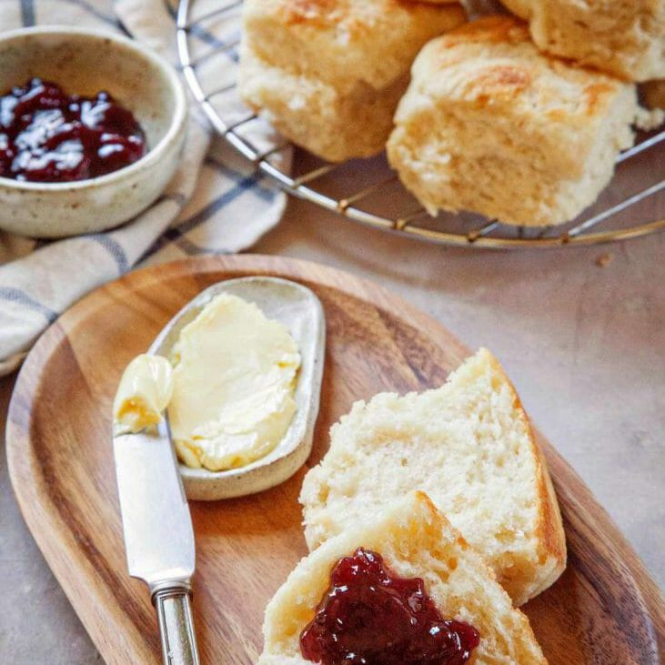 Angel biscuits with jam and butter on a wooden plate