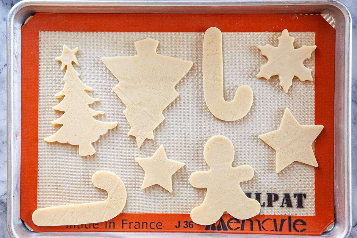 Silpat lined baking sheet with holiday themed Cut Out Sugar Cookies.