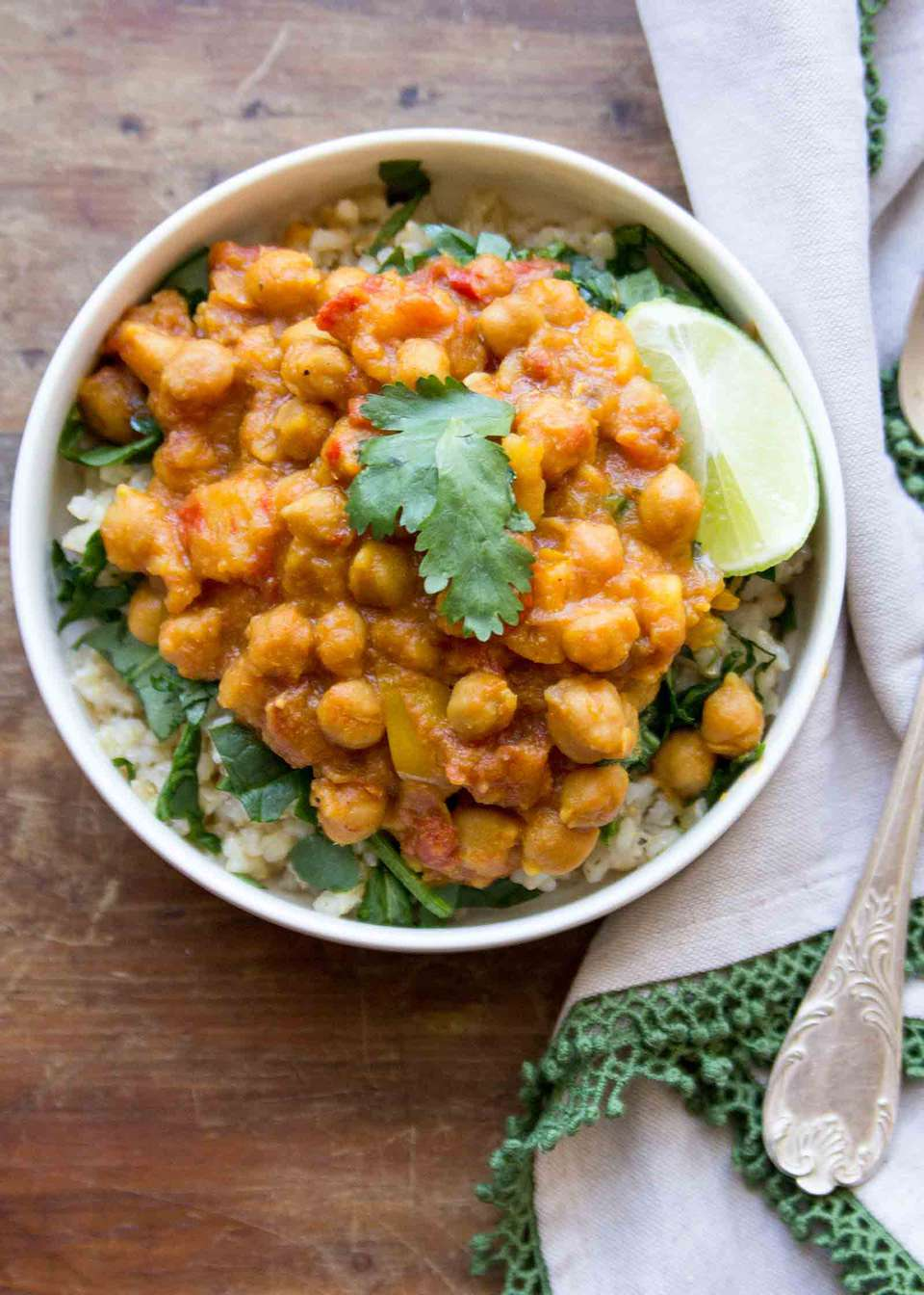 Crockpot Chickpea Curry served in a bowl with fresh spinach, rice, and a wedge of lime.
