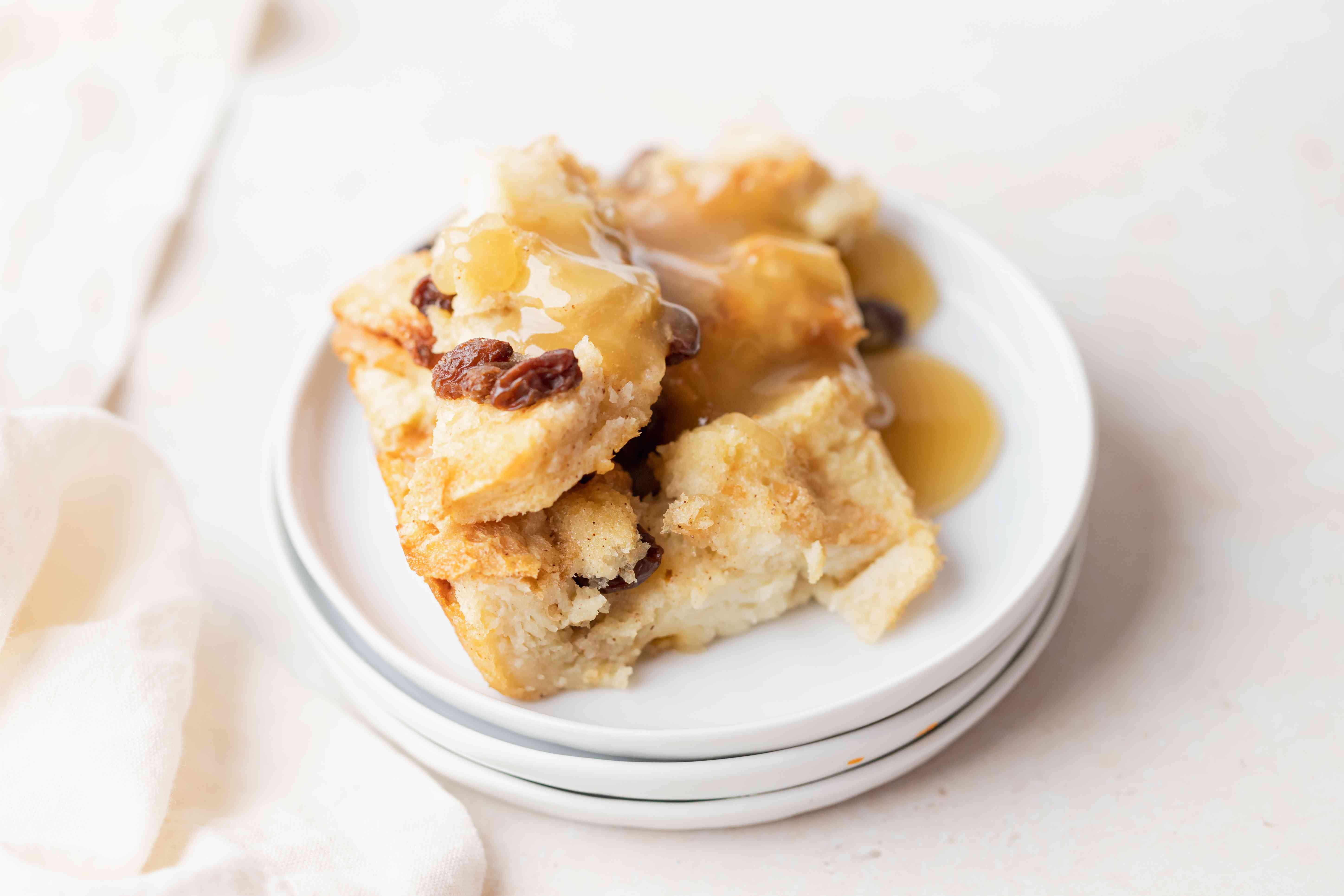 A stack of plates with easy bread pudding set on top.