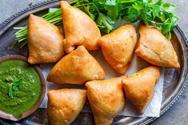 Vegetarian Samosas on a bed of herbs with one samosa filled with potato and peas alongside a cilantro mint chutney or dipping sauce in a small wooden bowl..