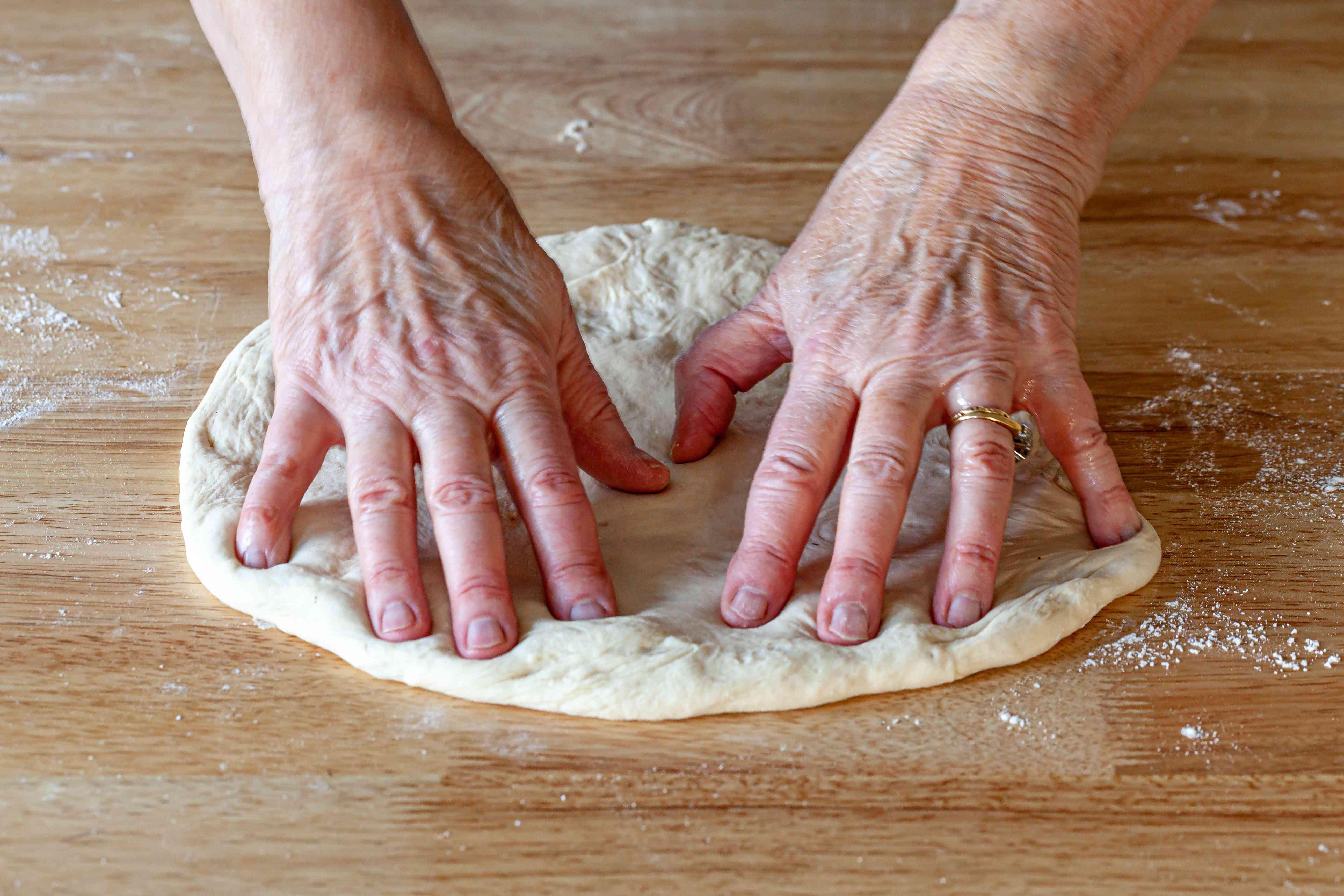 Pressing pizza dough into a circular shape.