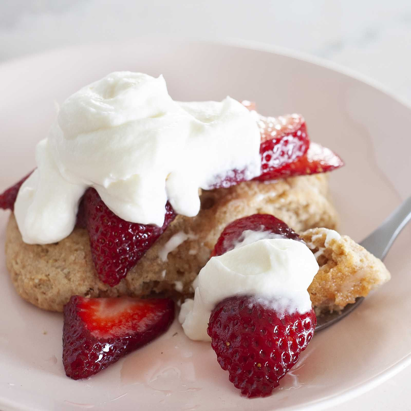 Close up view of healthy strawberry shortcake on a plate. A fork has sliced strawberries, whipped yogurt topping and shortcake on it.