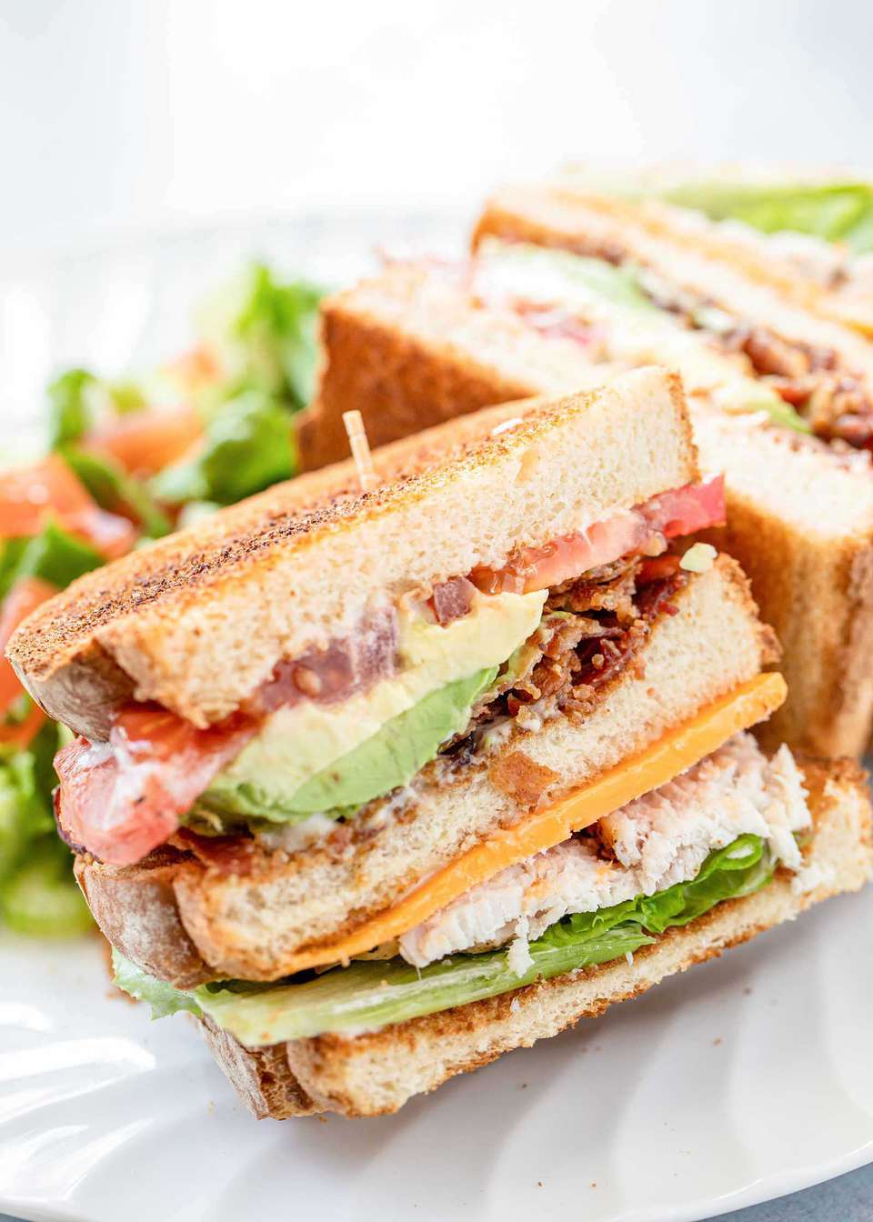 Side view of turkey club with garlic mayo on a plate. The bread is toasted and the mayo, avocado, bacon, tomato, lettuce and turkey are visible in the sandwich. A second half of the sandwich is behind the first.