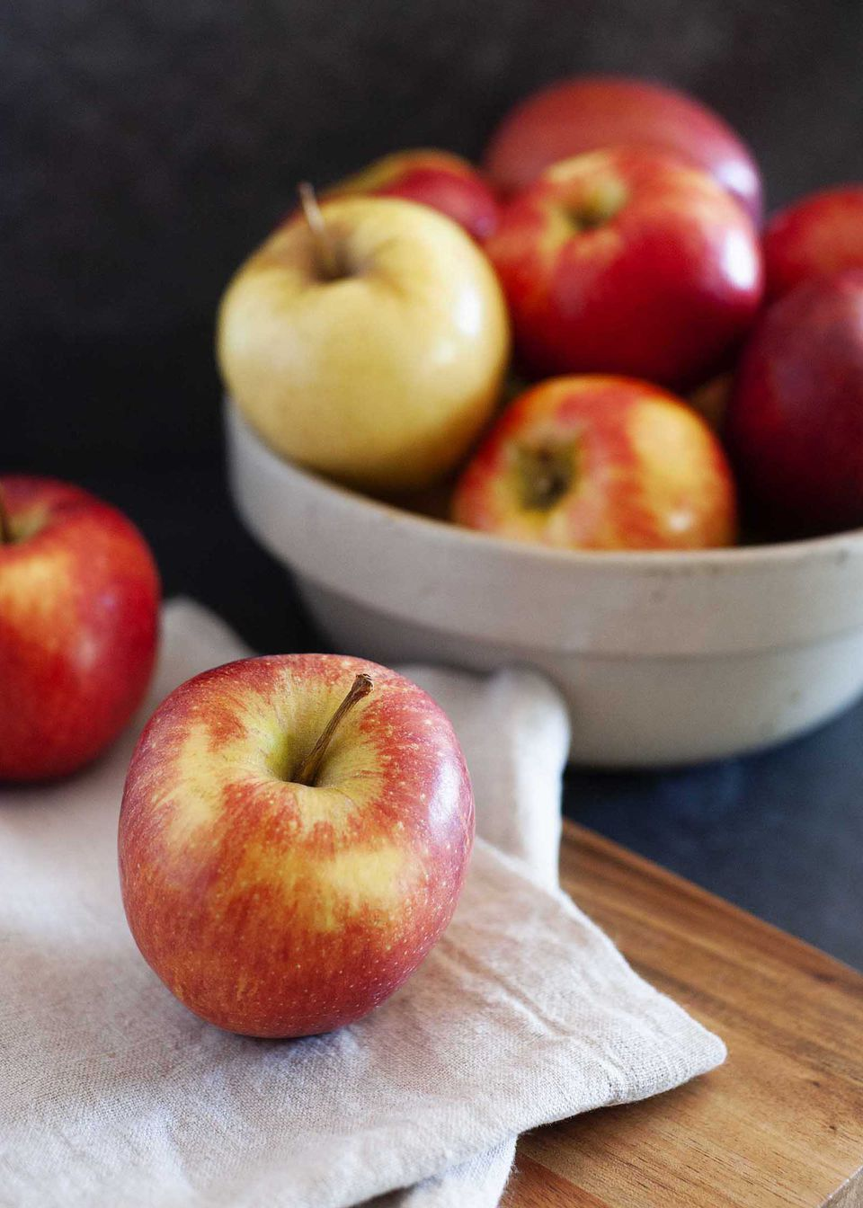 Guide to fall apples with apples on a counter and in a ceramic bowl.