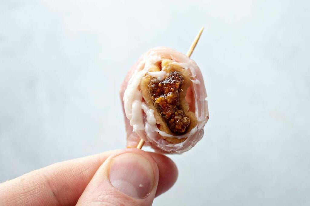 bacon wrapped around a dried fig on a toothpick