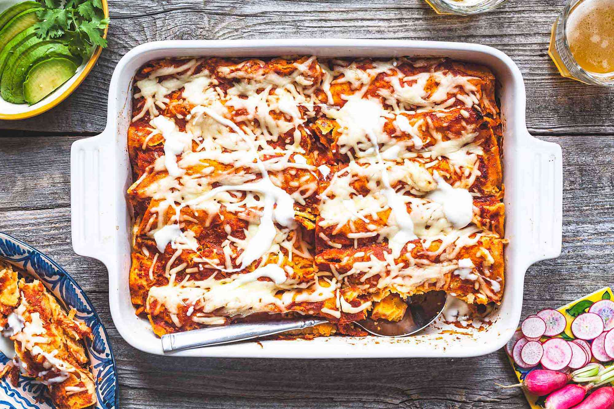 Casserole dish filled with easy vegetarian enchiladas fillled iwth butternut squash and topped with cheese
