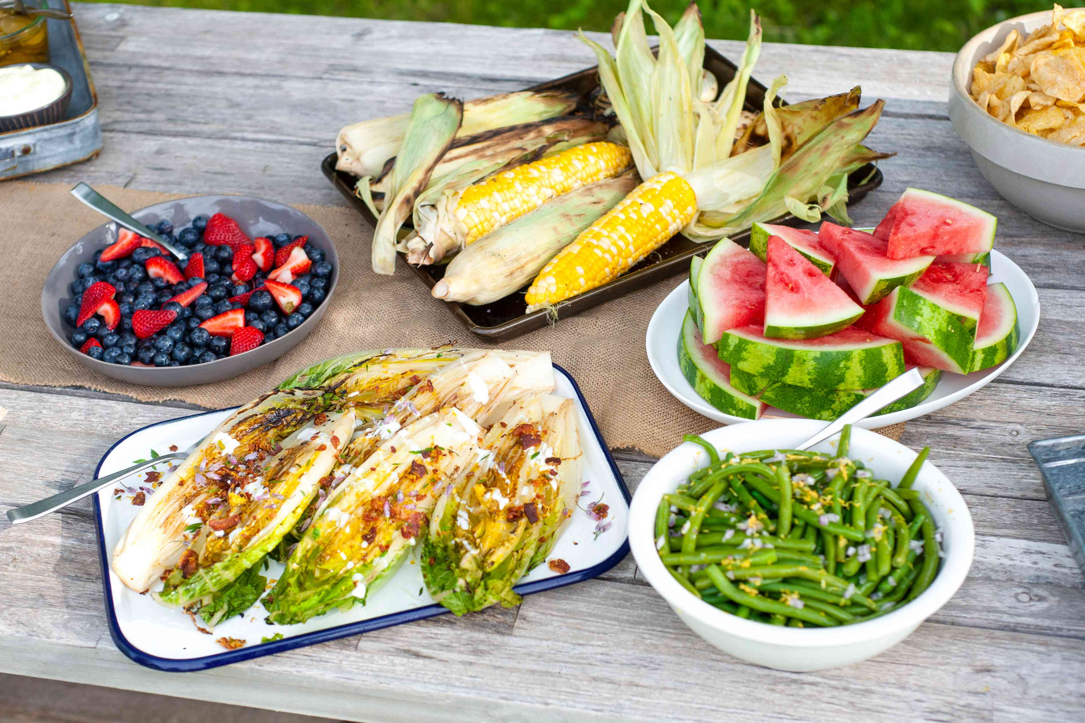 Picnic table full of grilled lettuce, corn, berries, watermelon and green beans.