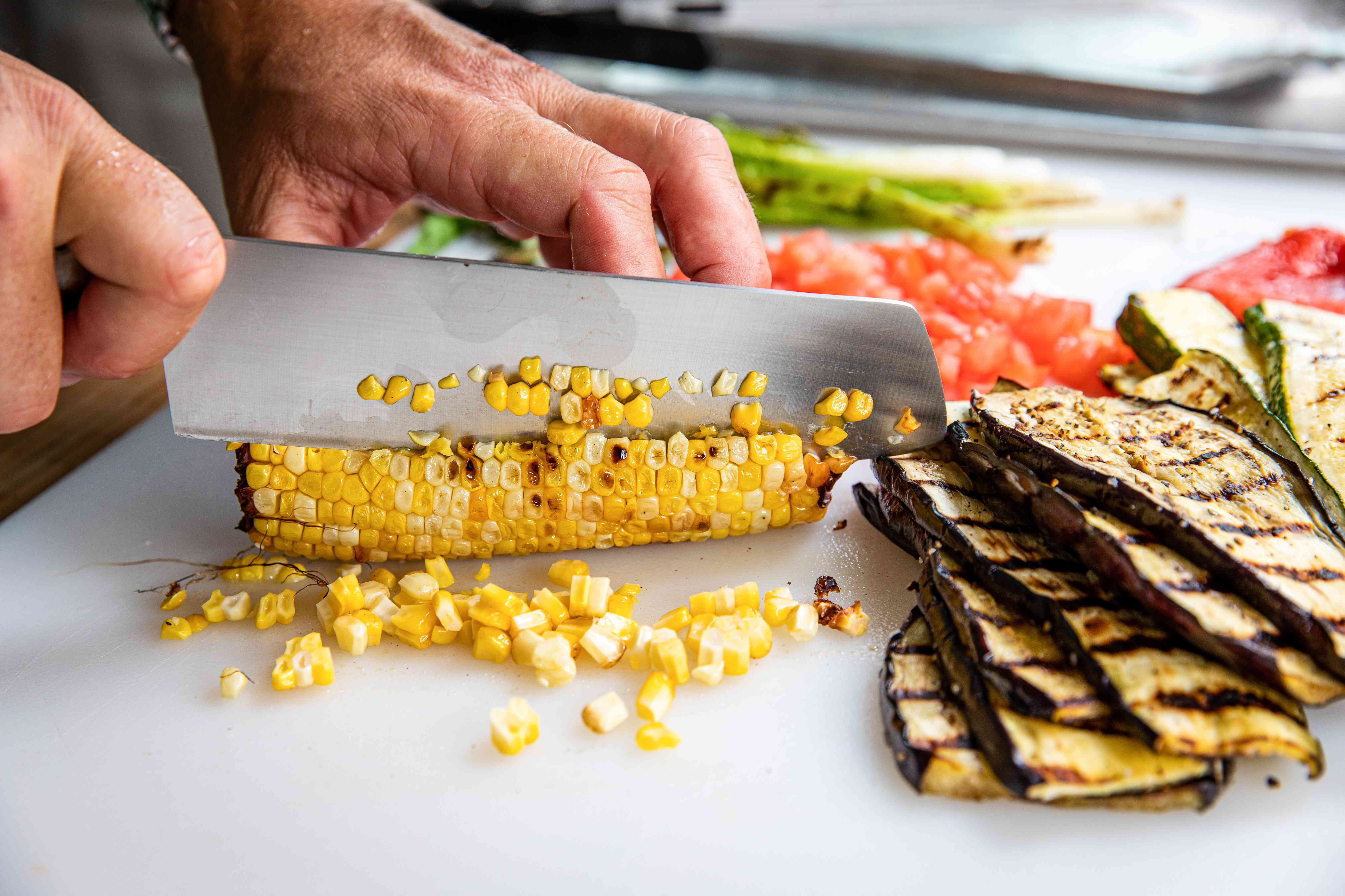 Cutting the kernels off a cob of corn for vegetable nachos.