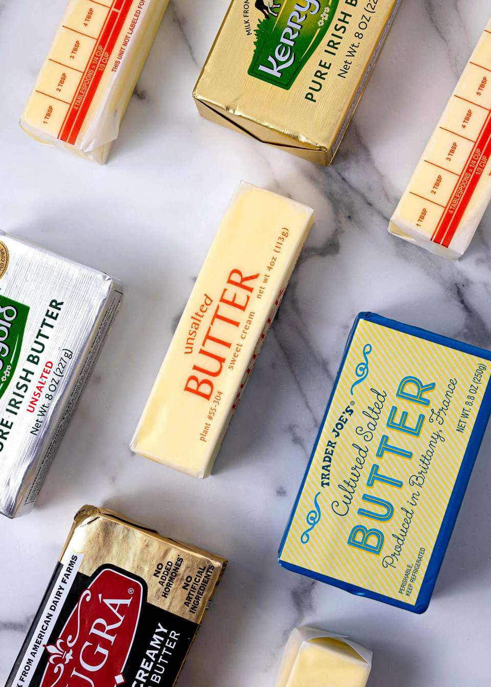 Unsalted and salted butter sticks on marble