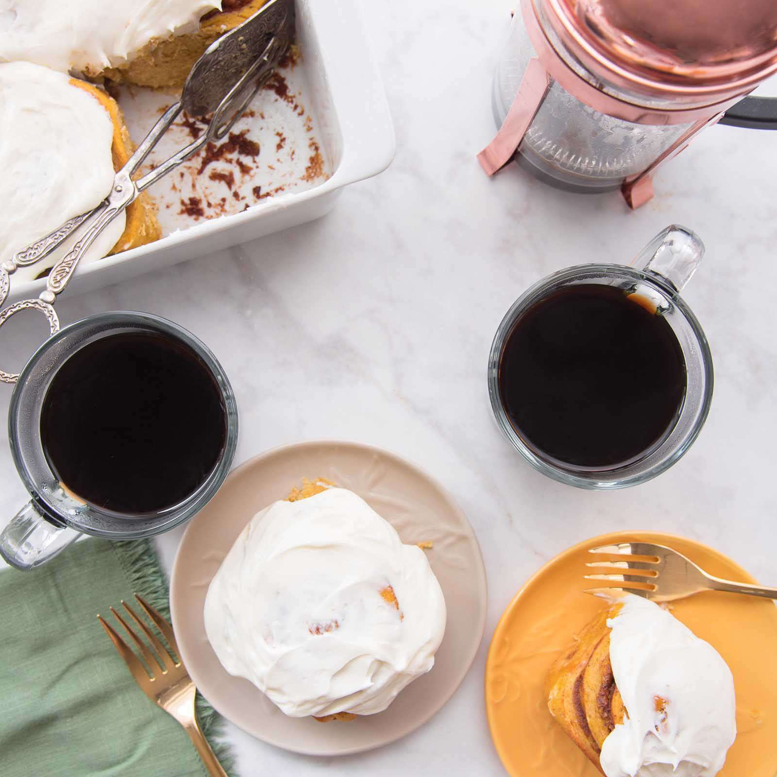 Overhead view of a table with Homemade Pumpkin Cinnamon Rolls served on plates with coffee, a french press, and the remaining rolls above the plates.