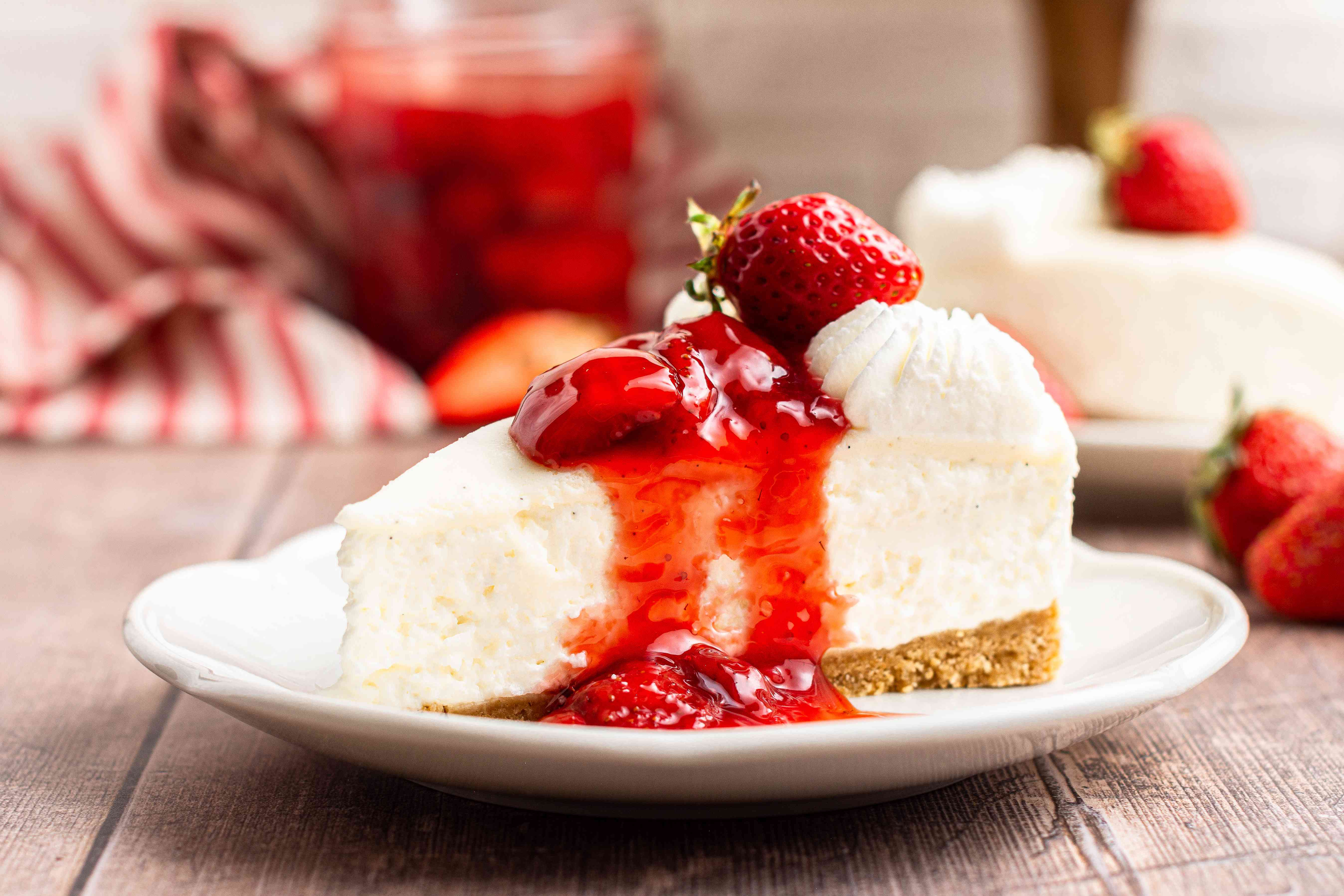 A side view of a plate with easy no bake cheesecake topped with strawberry preserves.
